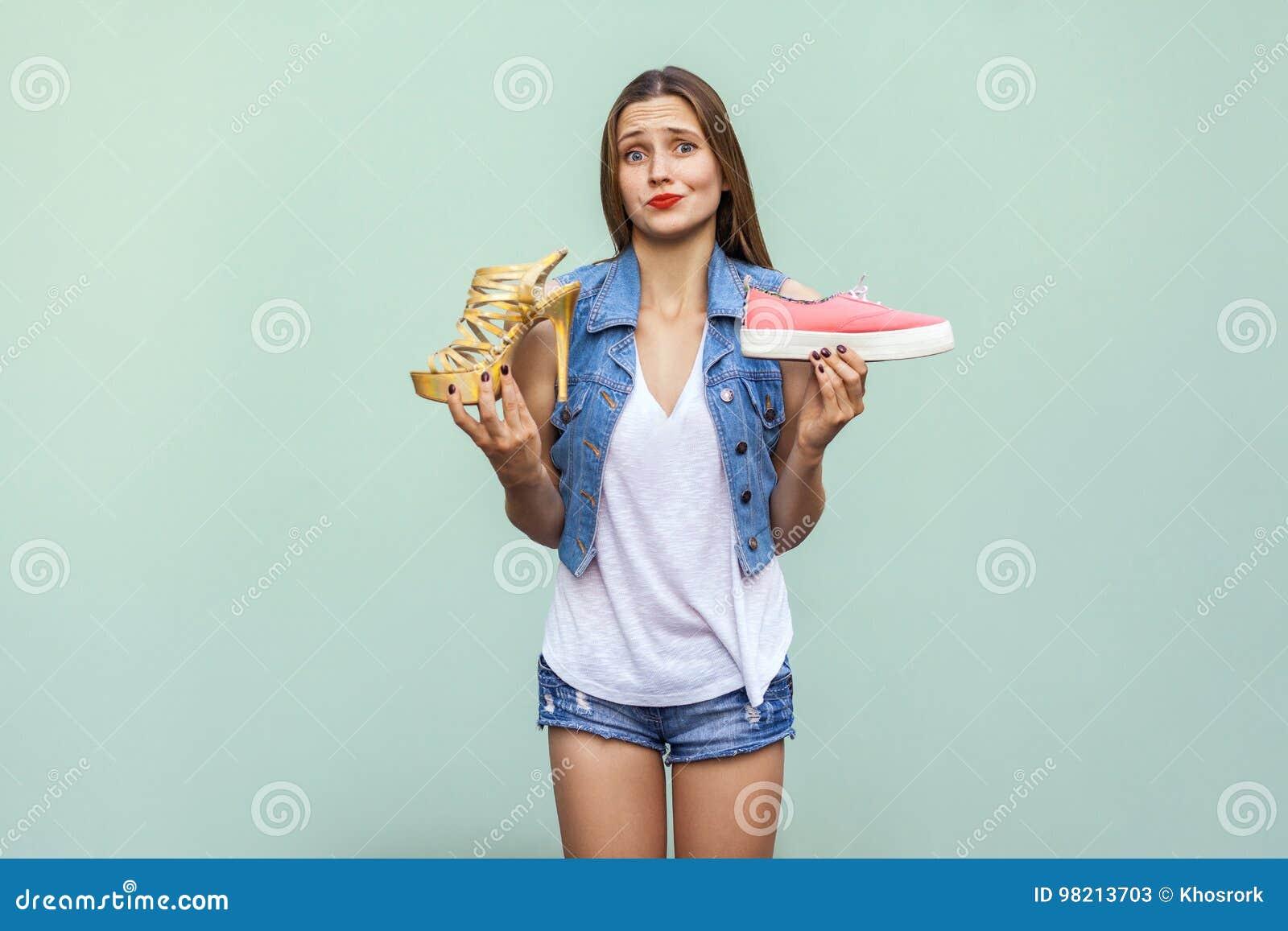 ... caucasiano bonita com sardas obteve de escolha as sapatilhas  confortáveis ou o salto alto incômodo mas considerável, de pensamento e de  vista a câmera O ... 3ac4c1cffe