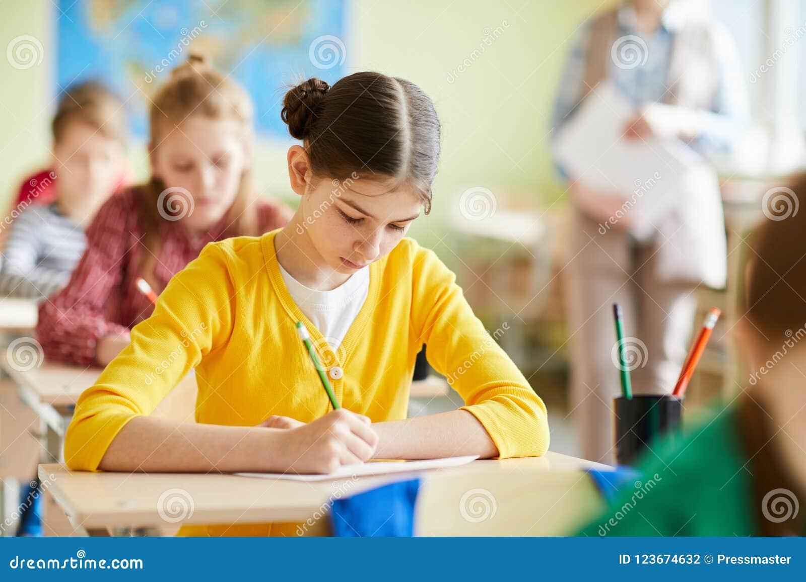 Menina ocupada do estudante concentrada no questionário