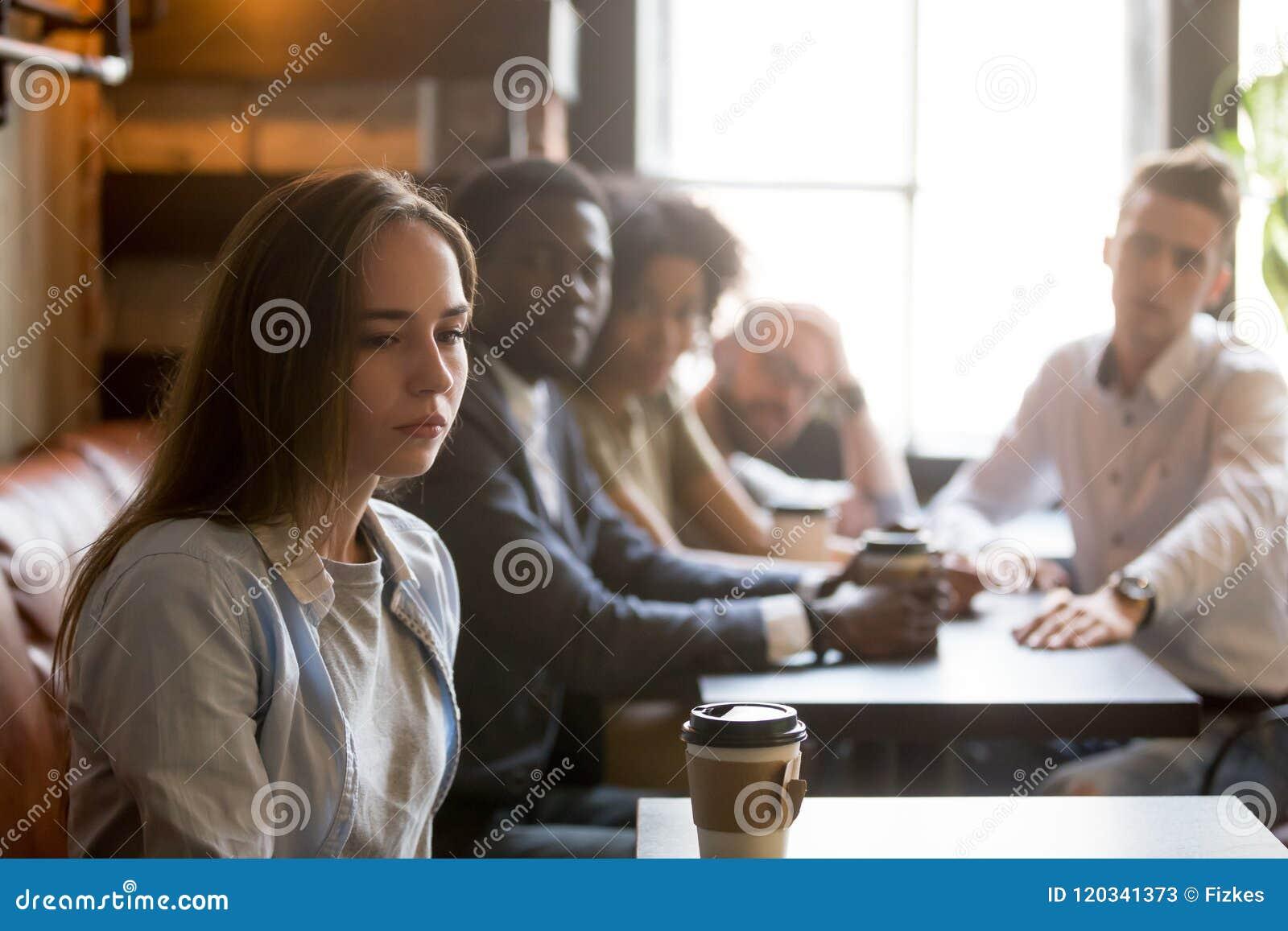 Menina ofendida que ignora os amigos que desculpam-se após o gracejo mau