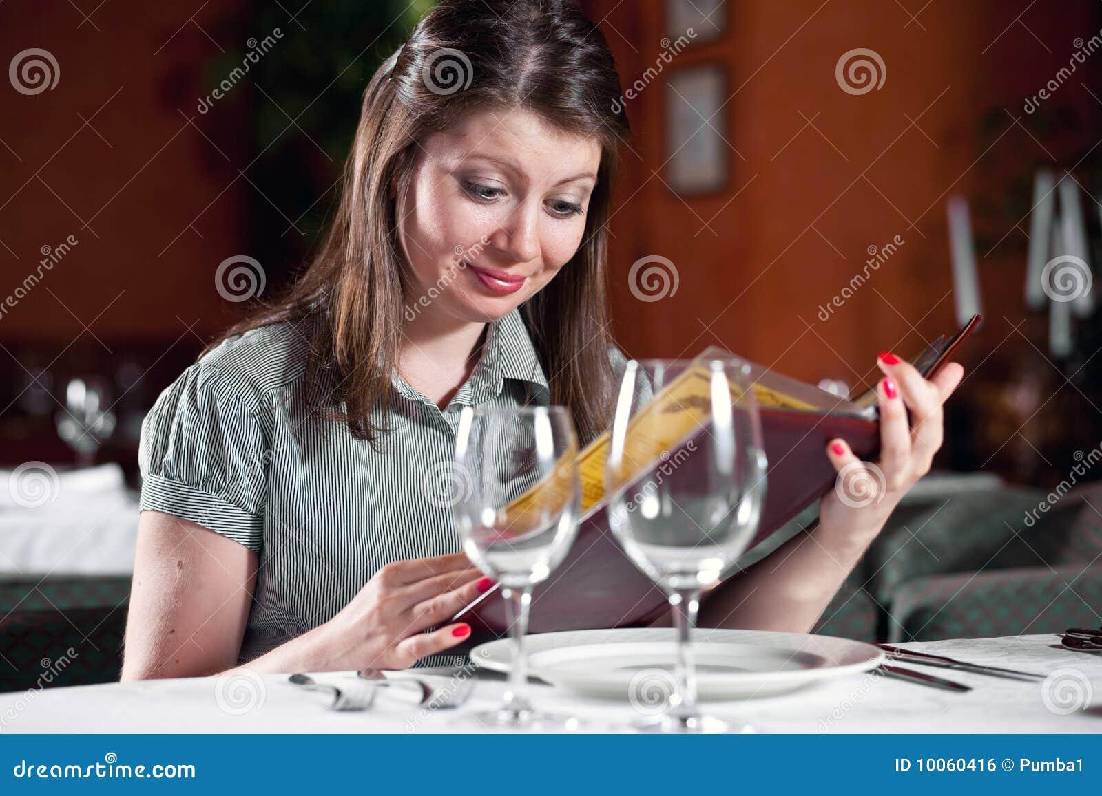 A menina olha no menu no café