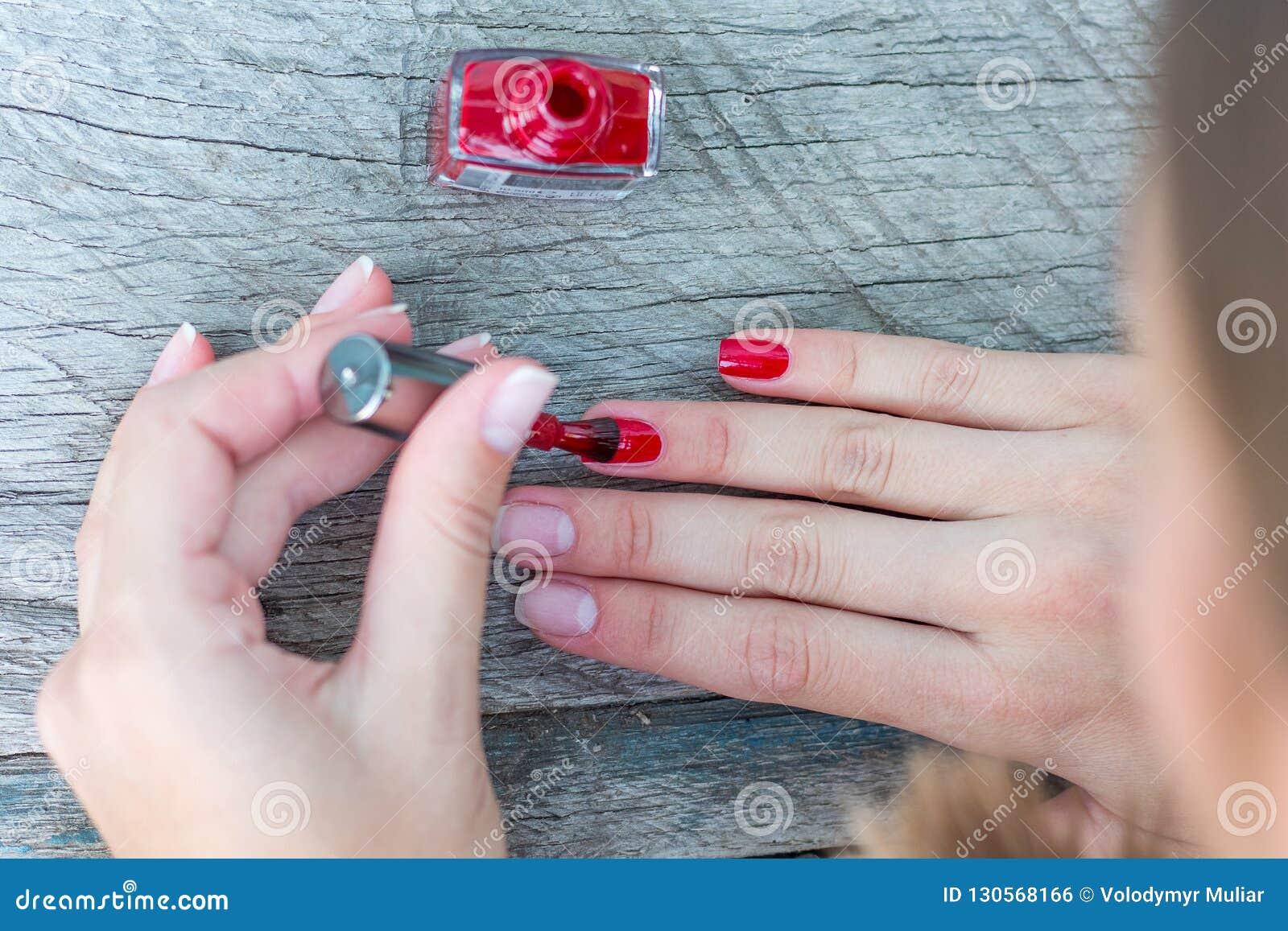 A menina põe uma laca preta sobre seu nails_