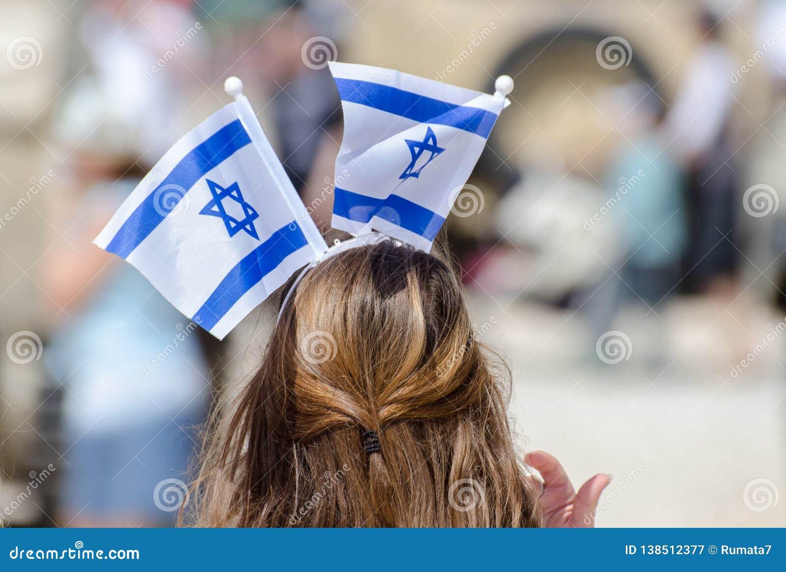 A menina patriótica com a bandeira israelita em sua cabeça comemora o dia de Israel Independence