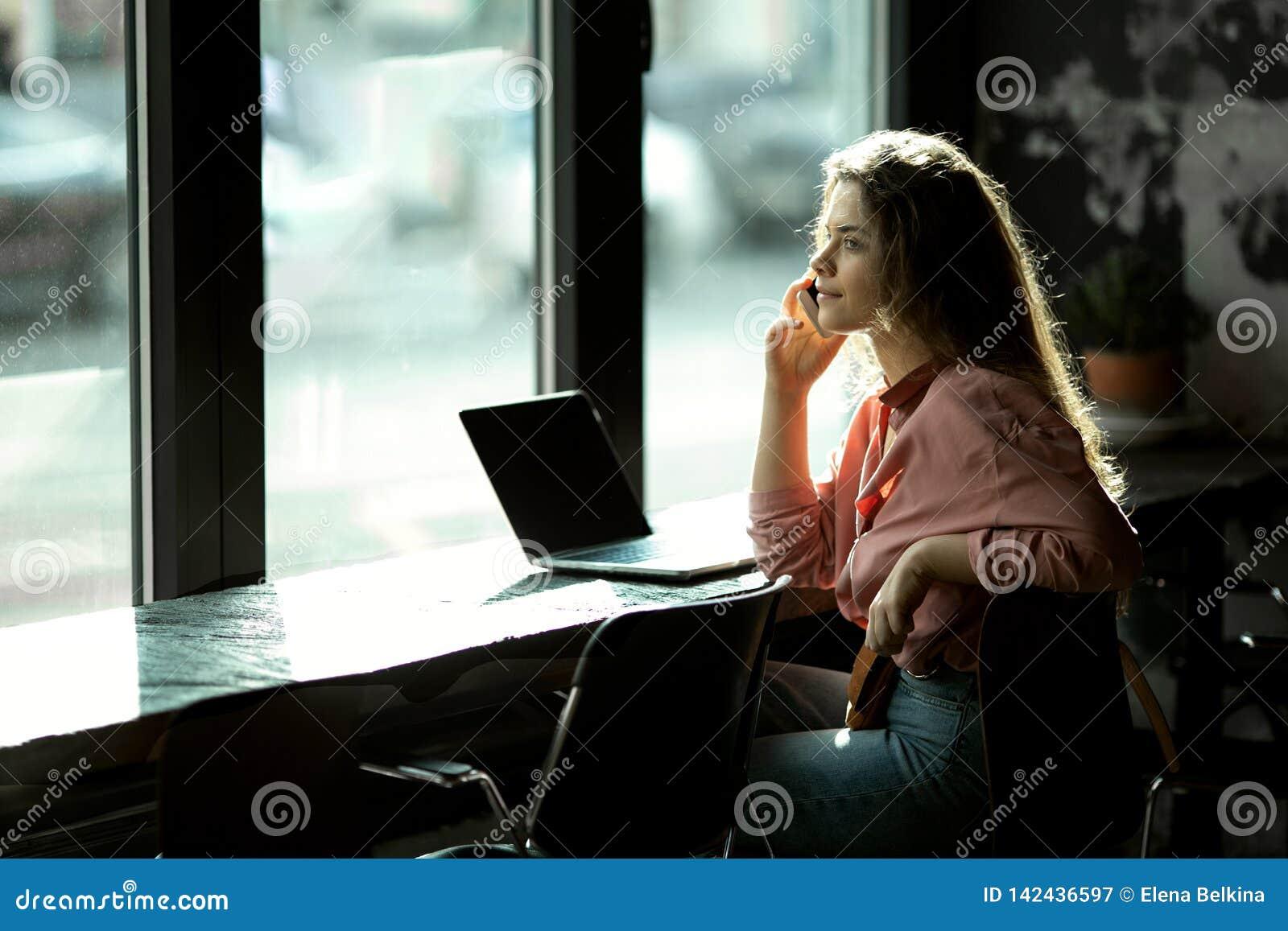 Menina pela janela em um café