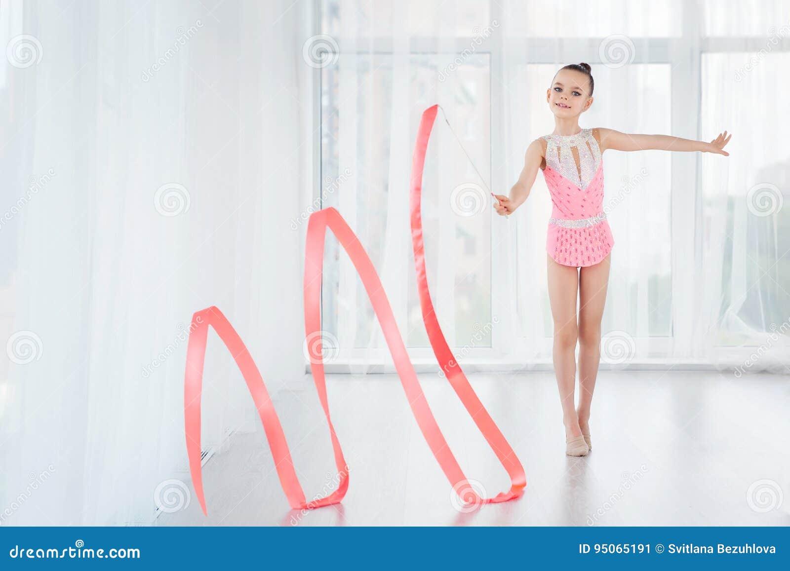A menina pequena bonita da ginasta no vestido cor-de-rosa do sportswear, fazendo o exercício da ginástica rítmica espirala com fi