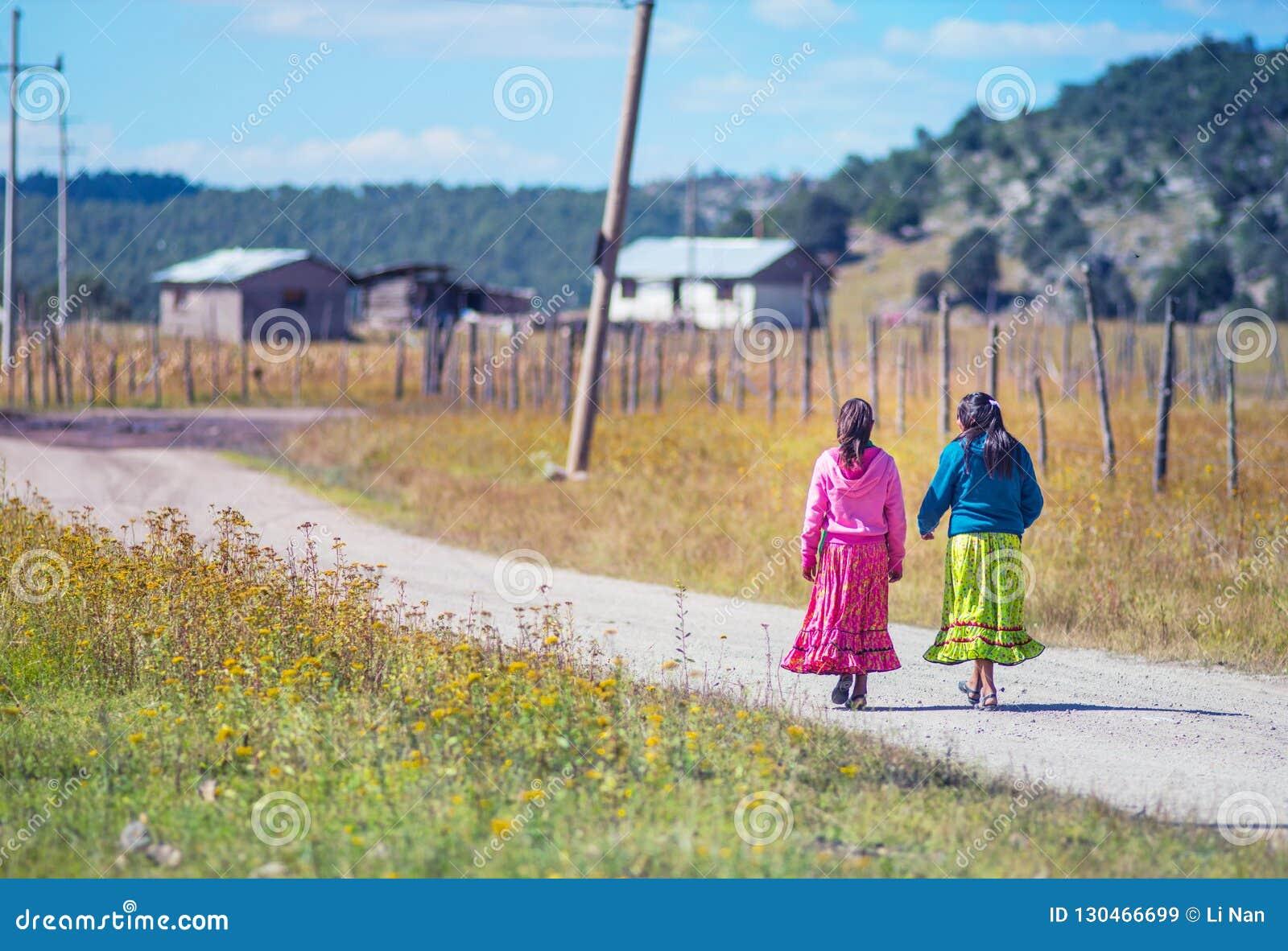 Menina pobre nativa da escola na caminhada colorida tradicional do vestido na maneira de dirigir, México, América