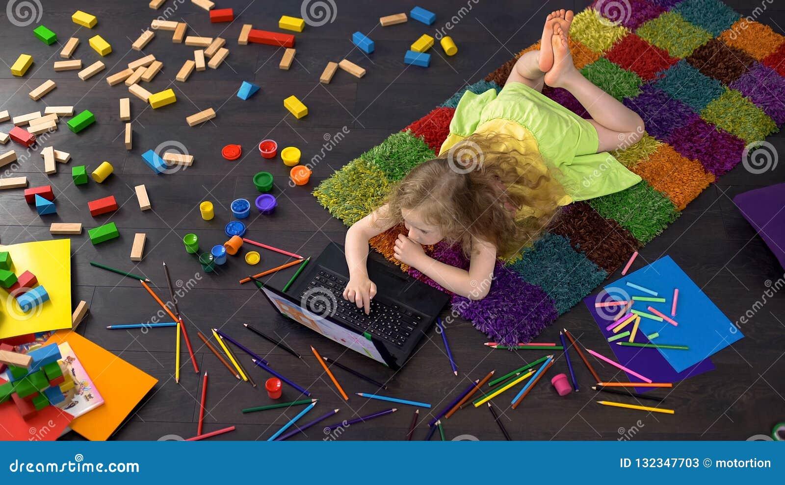 Menina pré-escolar que aprende letras no portátil, software educacional, infância