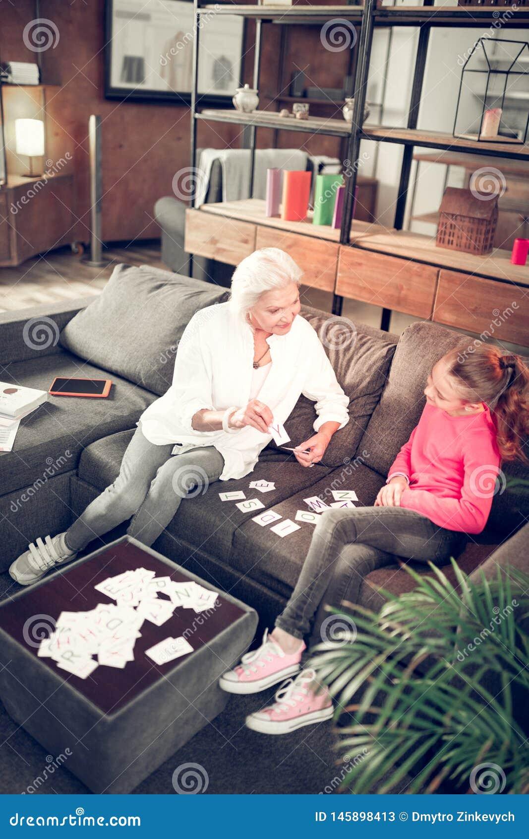 Menina pré-escolar que estuda letras com sua avó de inquietação