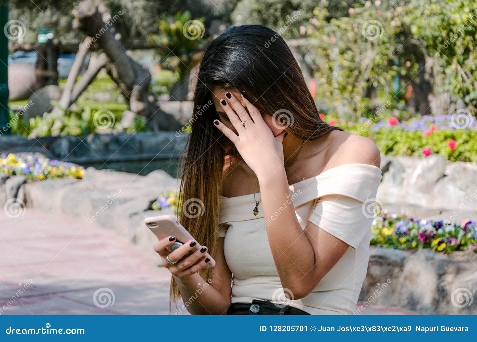 Menina preocupada do adolescente do moderno que olha seu telefone esperto em um parque