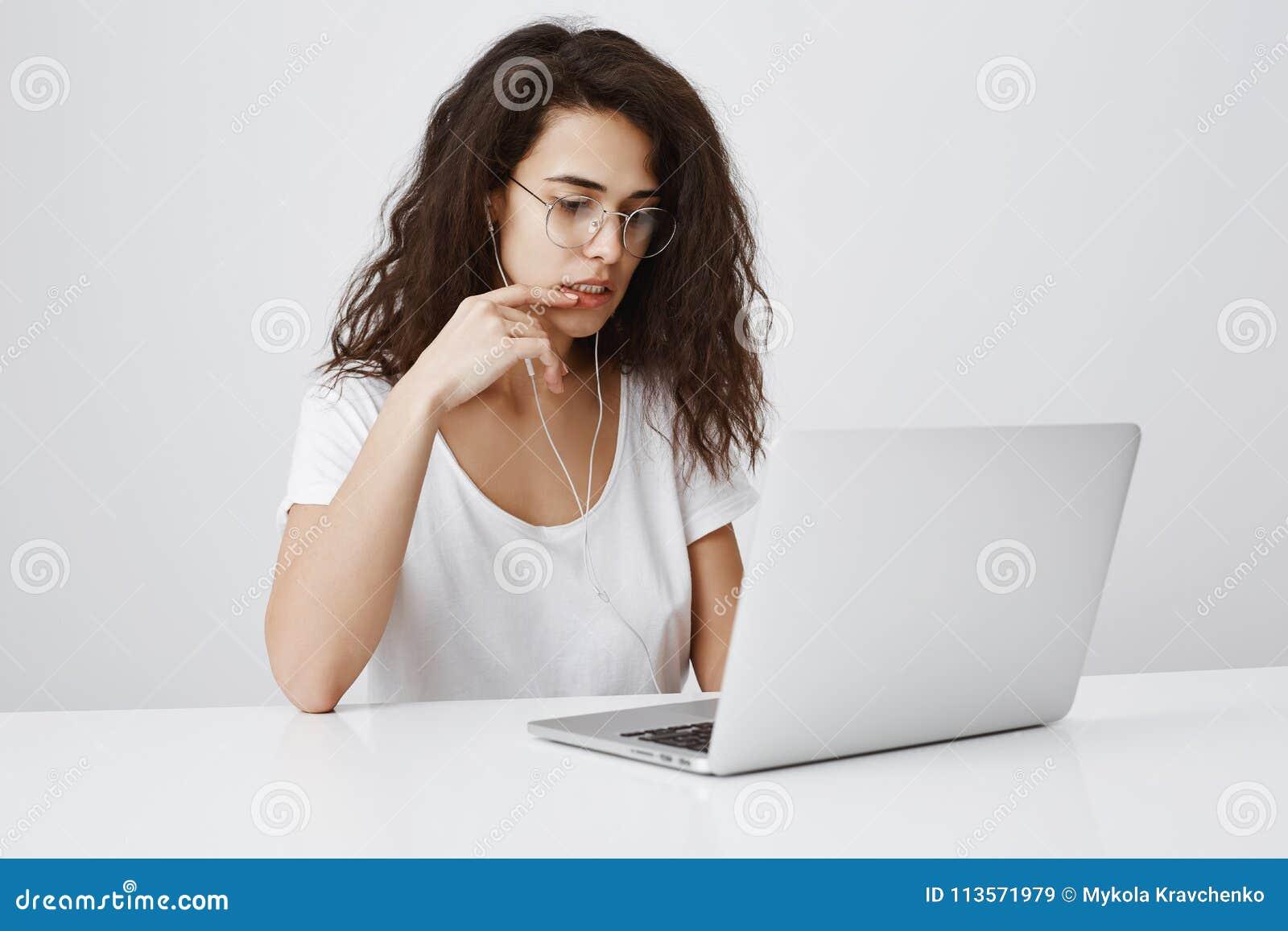 A menina preocupada encontrou o erro em seu projeto durante o trabalho no escritório Retrato da fêmea encaracolado-de cabelo conf
