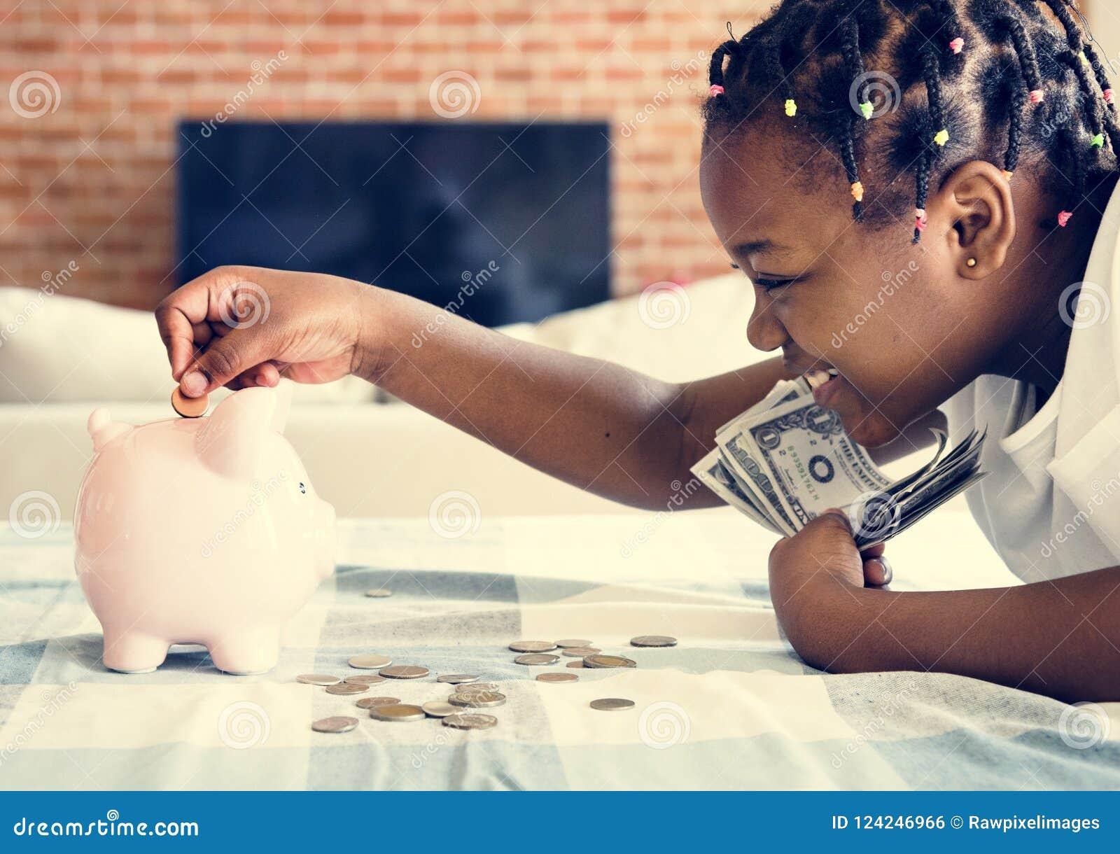 Menina preta que recolhe o dinheiro ao mealheiro