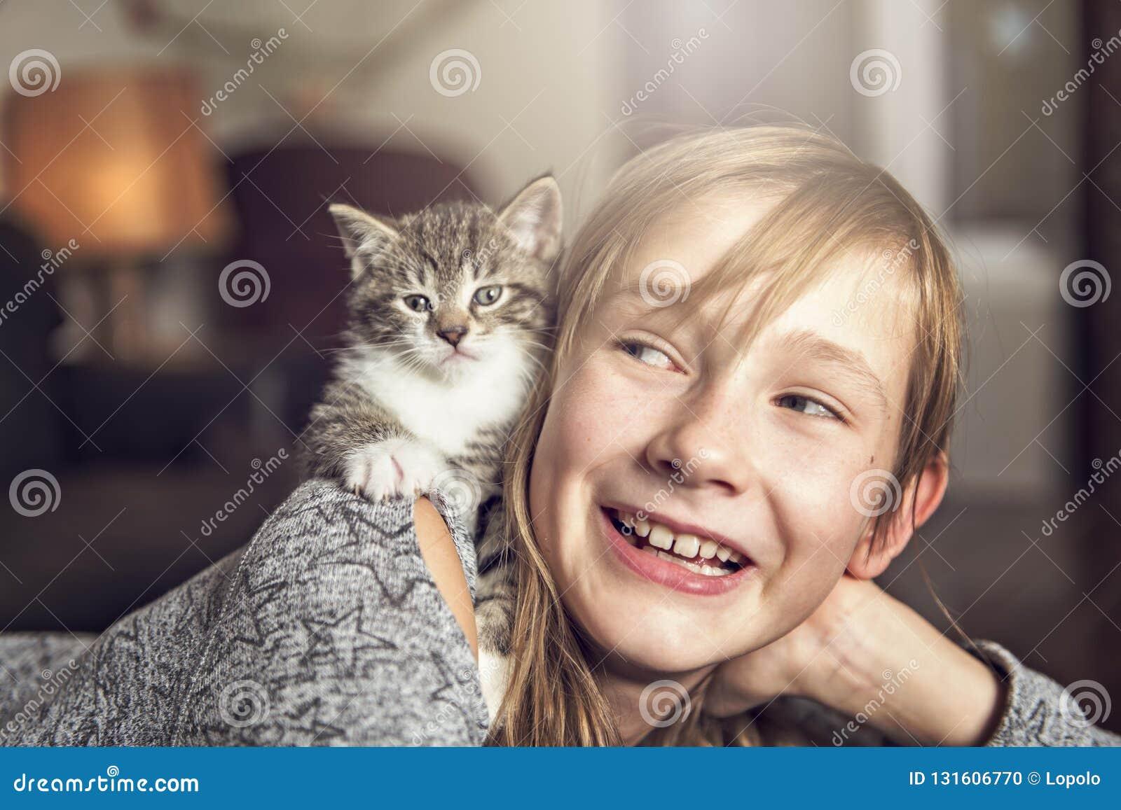 Menina Preteen de 10 anos velho com seu animal de estimação do gato no sofá