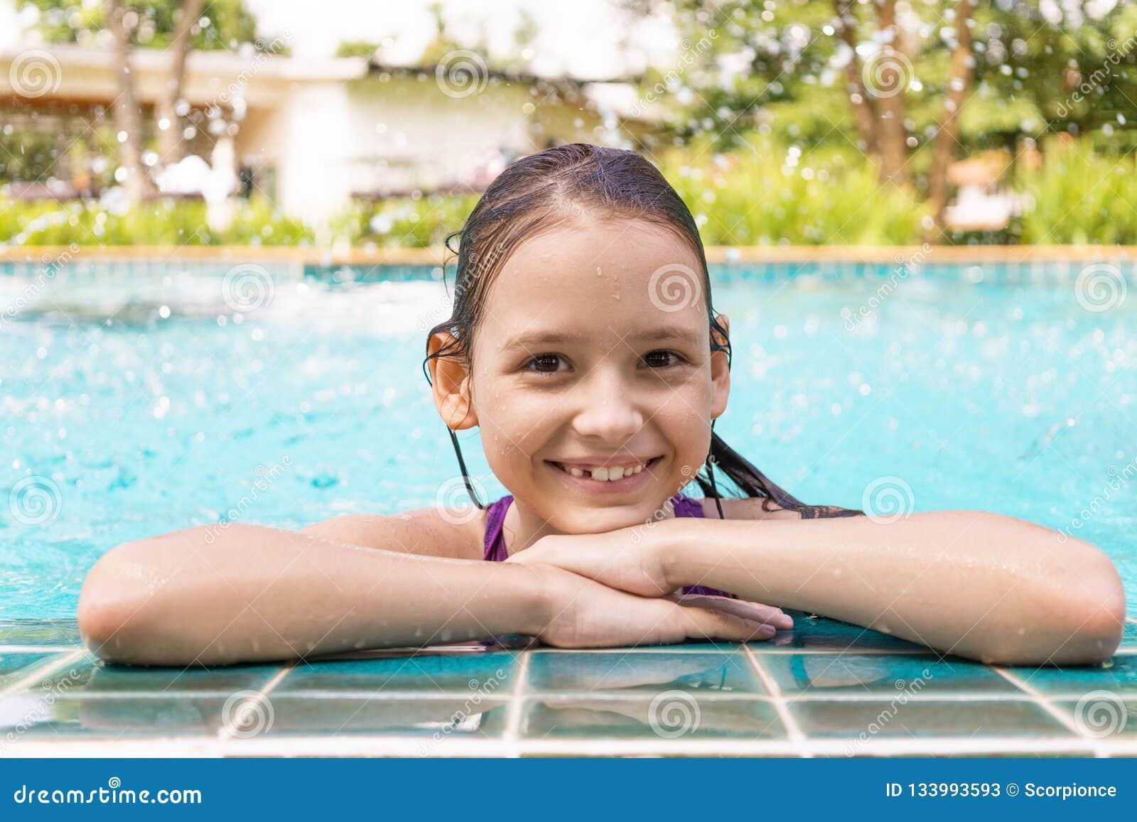 Menina preteen de sorriso bonito na borda da piscina Curso, férias
