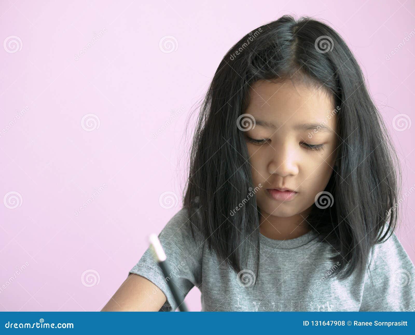 Menina principal desarrumado que escreve um livro com espaço cor-de-rosa do fundo e da cópia