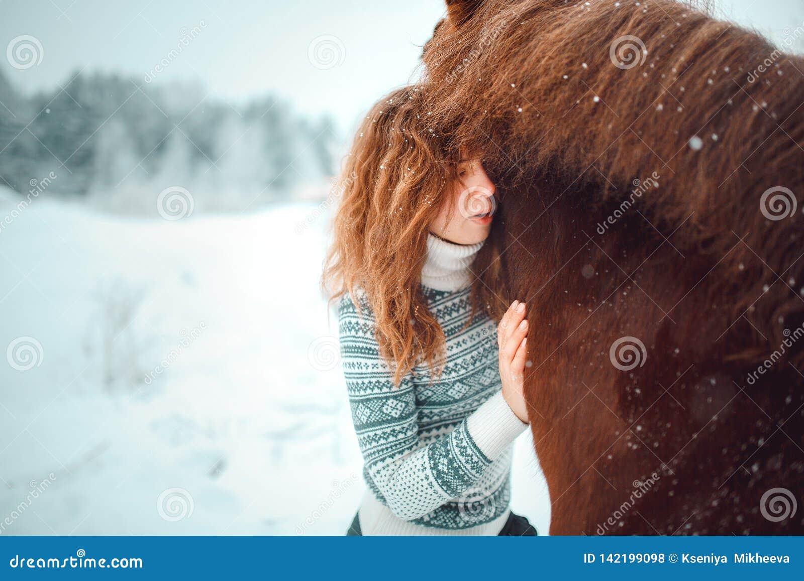 Menina principal vermelha com um cavalo em um campo da neve no inverno