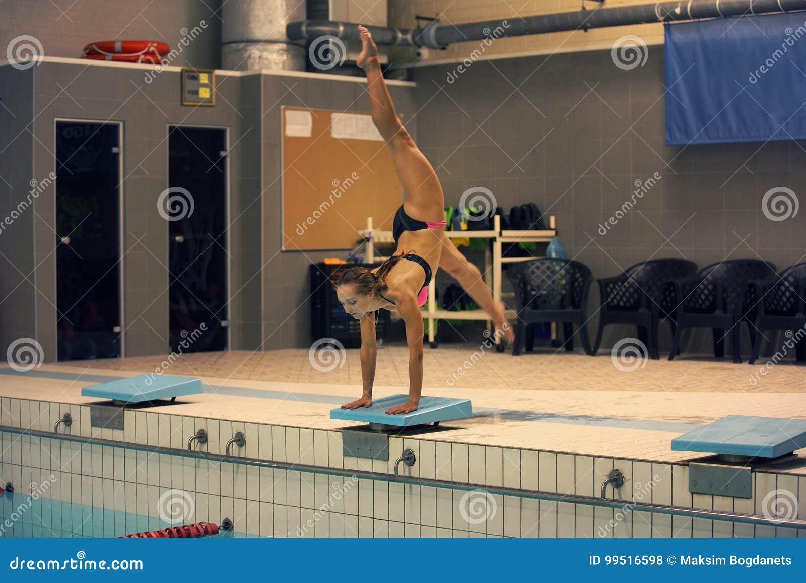 Menina pronta para saltar na piscina do esporte interno estar nos braços com pés acima