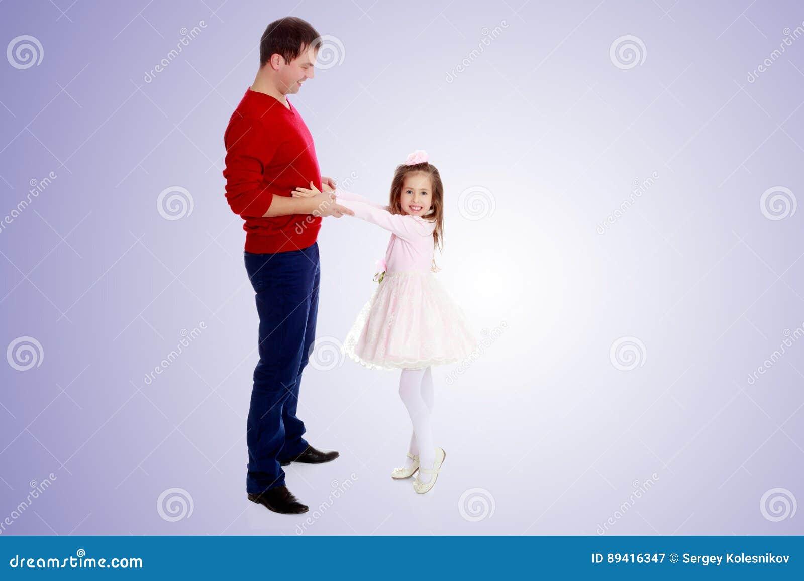 A menina puxa suas mãos para seu paizinho