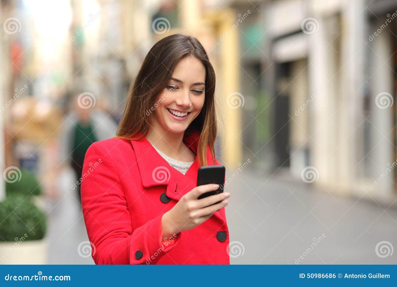 Menina que anda e que texting no telefone esperto na rua no vermelho