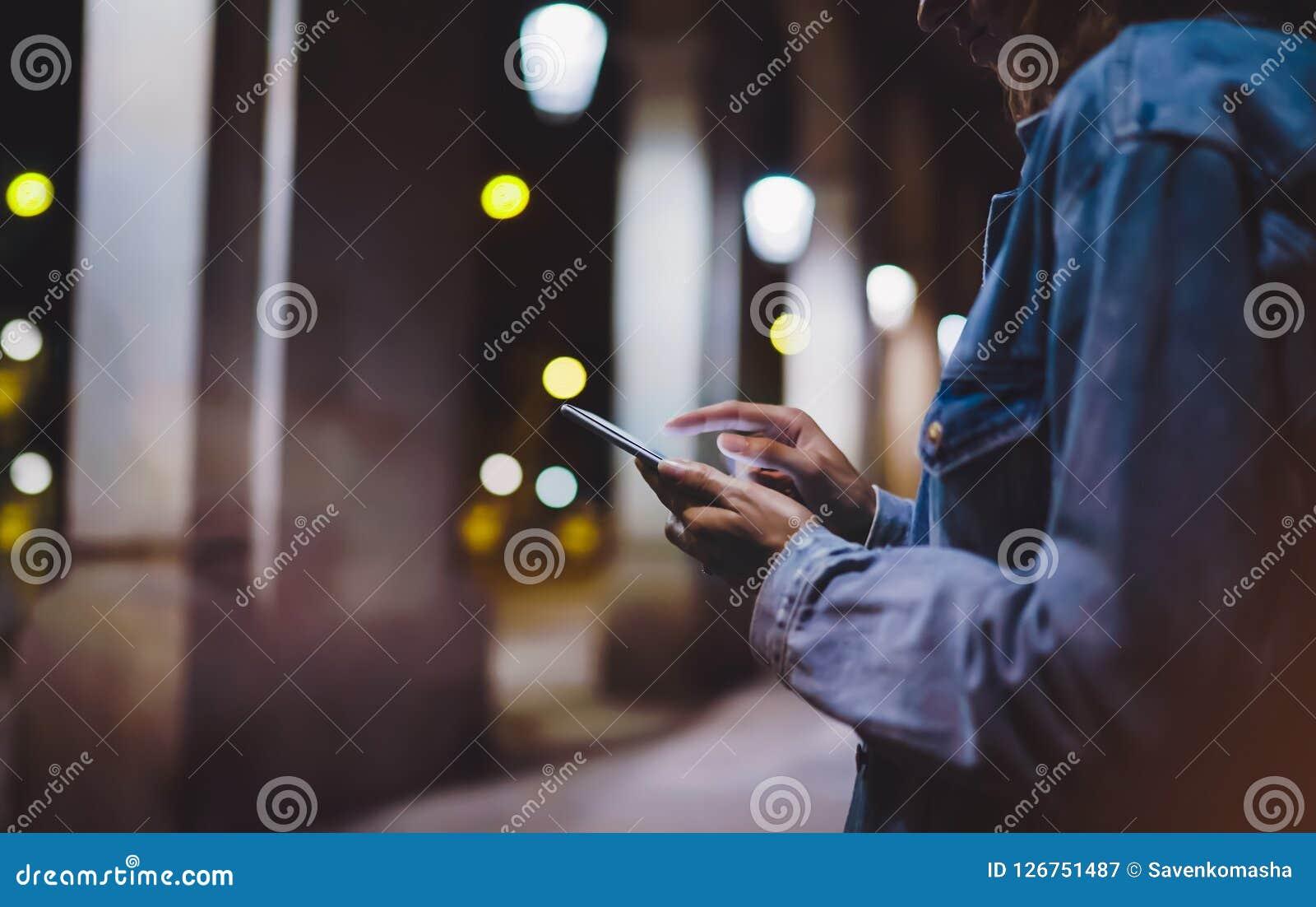 Menina que aponta o dedo no smartphone da tela na luz na cidade atmosférica da noite, utilização do bokeh do fulgor da iluminação