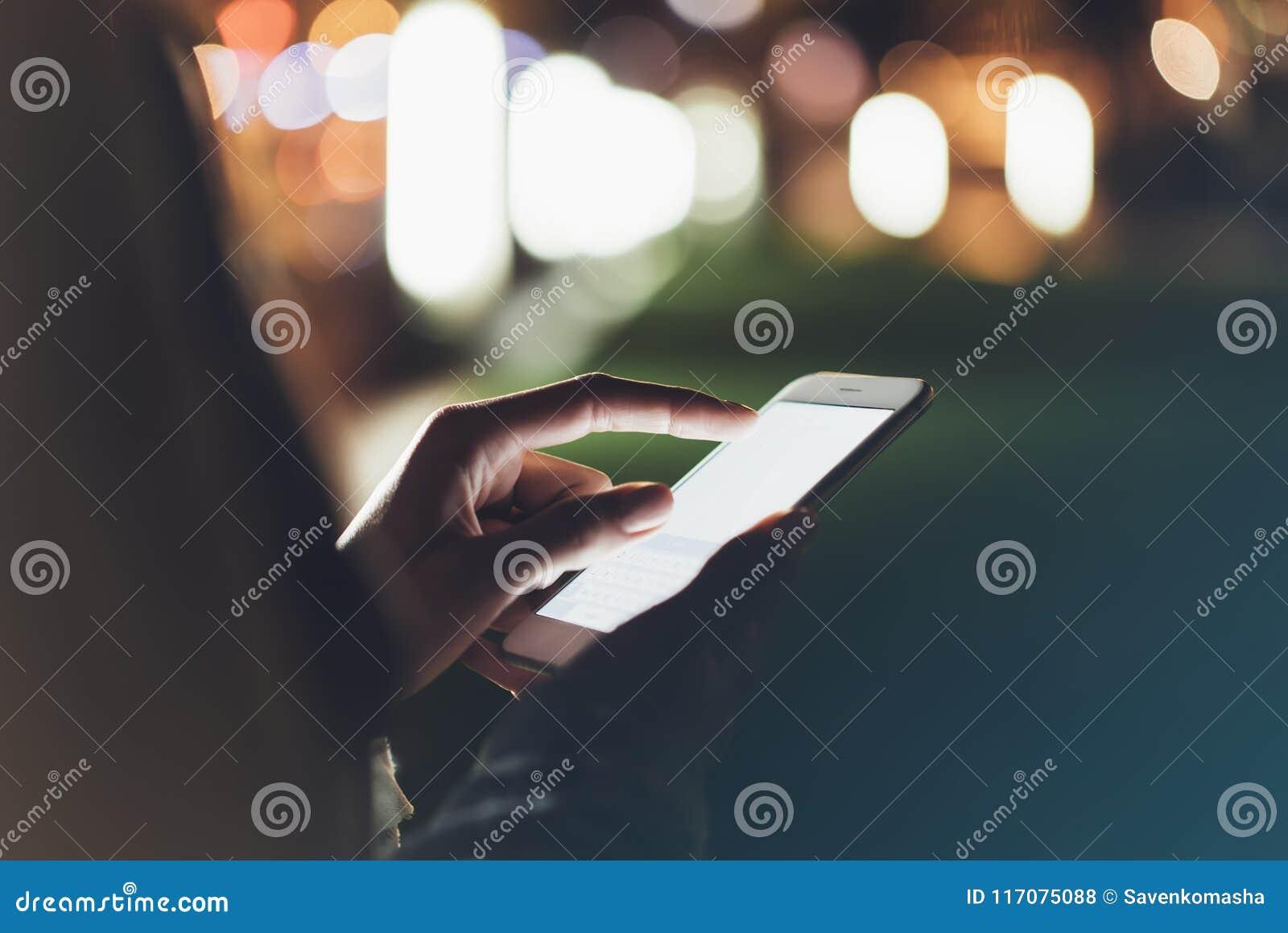 Menina que aponta o dedo no smartphone da tela na luz da cor do bokeh da iluminação do fundo na cidade atmosférica da noite, mode