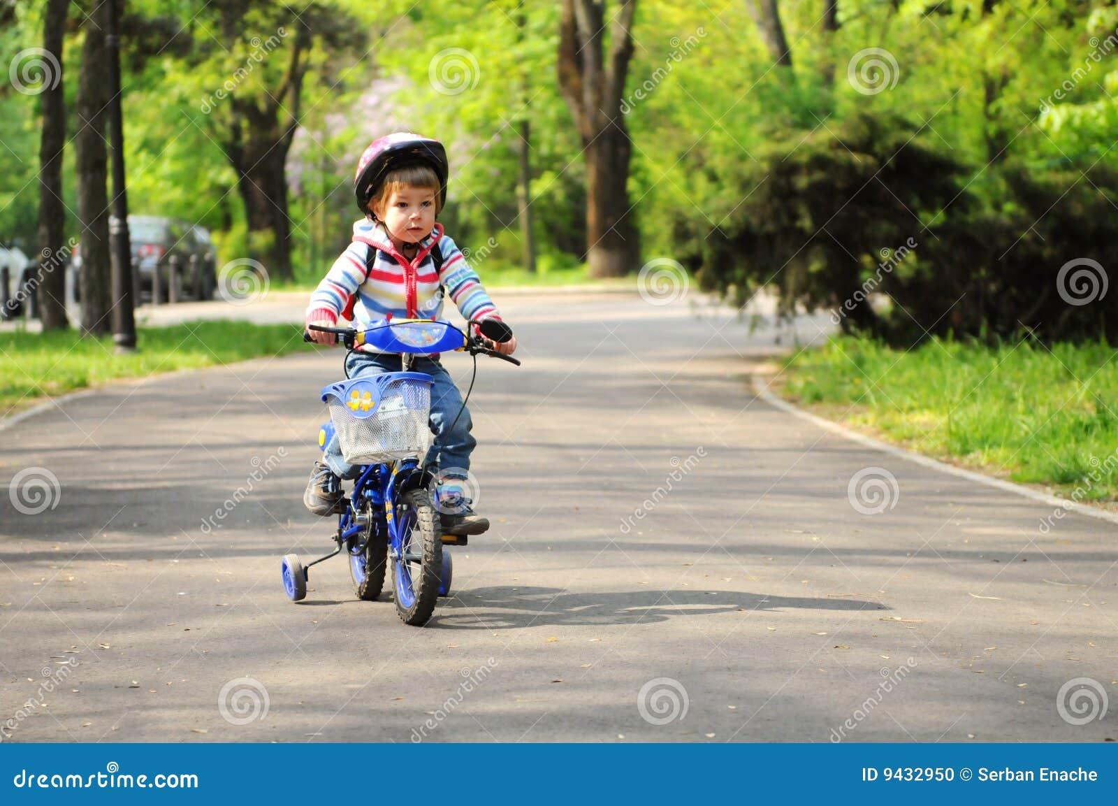 Menina que aprende montar a bicicleta