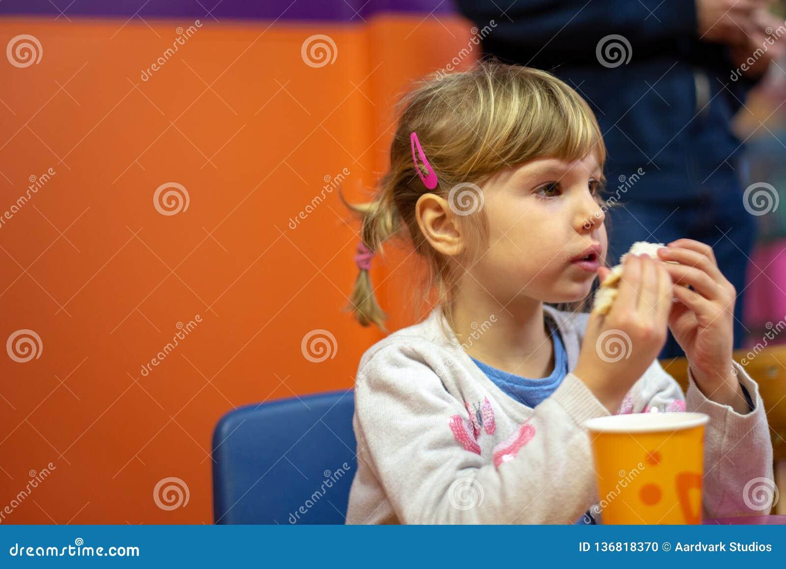 Menina que come o sanduíche na festa de anos