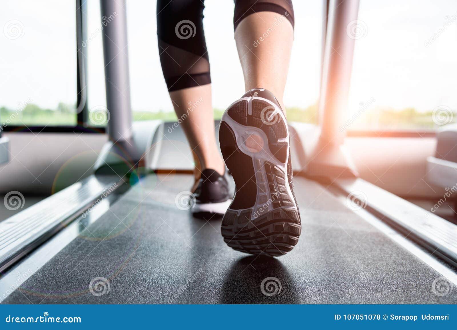 Menina que corre na escada rolante, mulher da aptidão com pés musculares em g