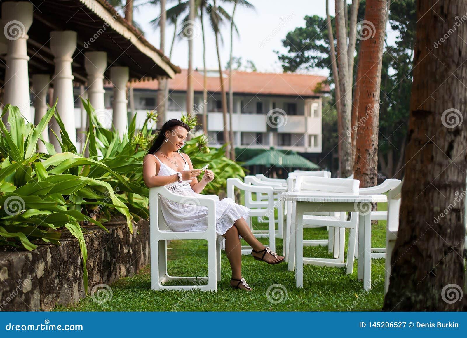 Menina que descansa no gramado noiva na lua de mel Territ?rio do hotel ?rea do abrandamento Mulher que senta-se em um gramado ver