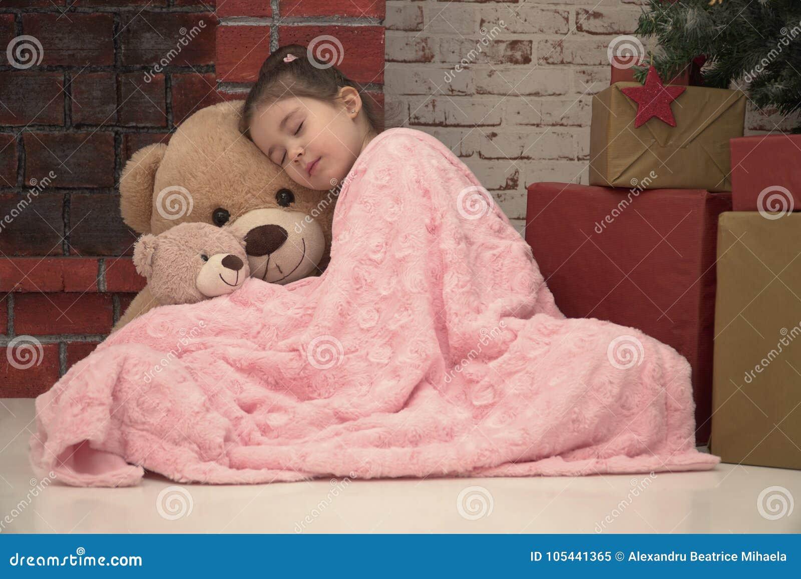 Menina que dorme com o urso enorme do luxuoso no assoalho Santa de espera