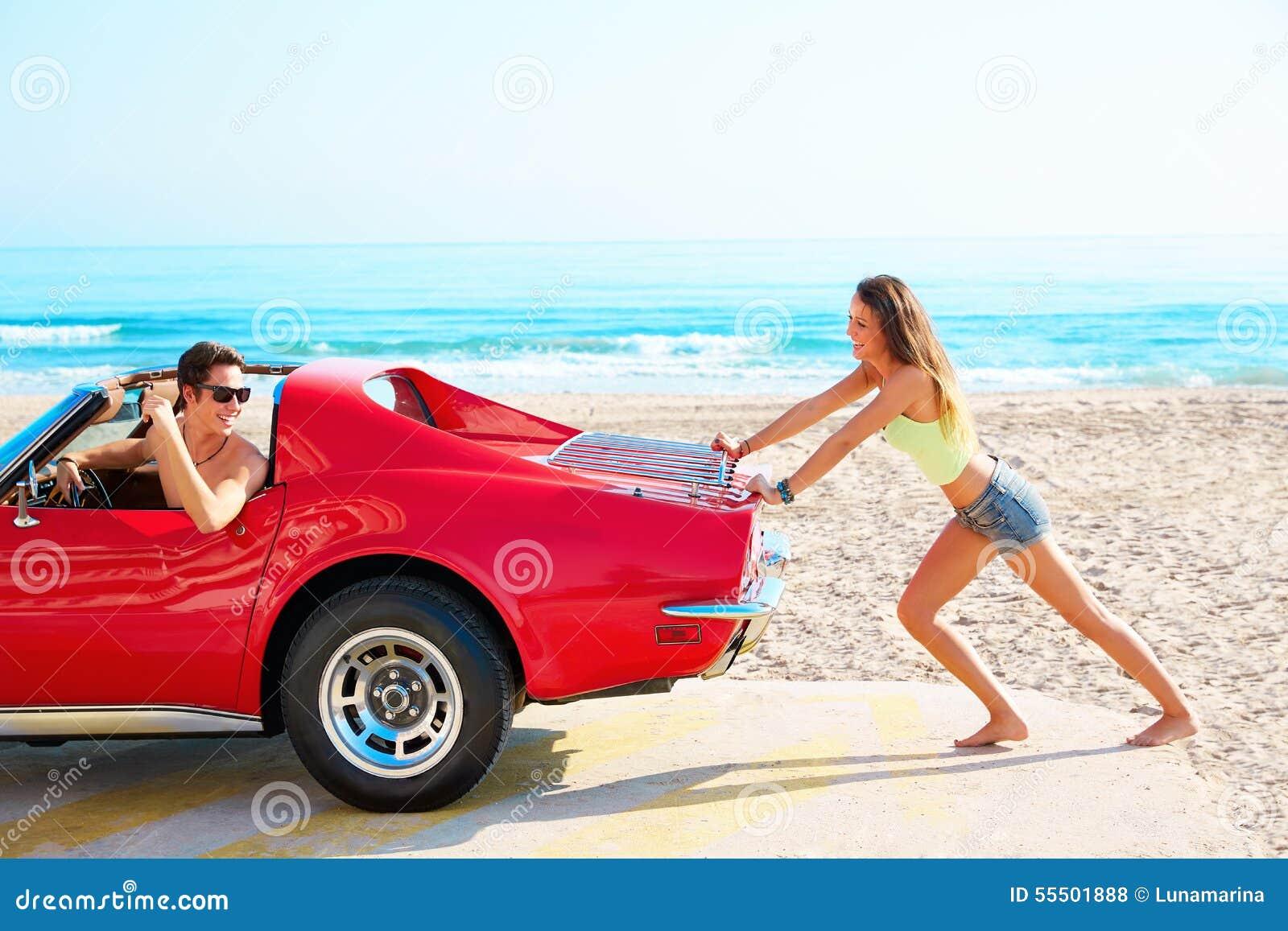 Menina que empurra um carro quebrado no indivíduo engraçado da praia