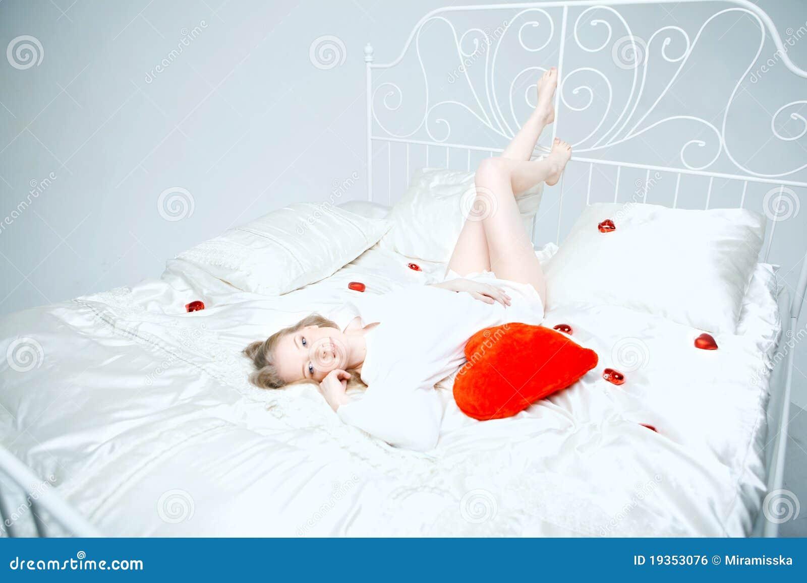 Menina que encontra-se na cama com um coração vermelho