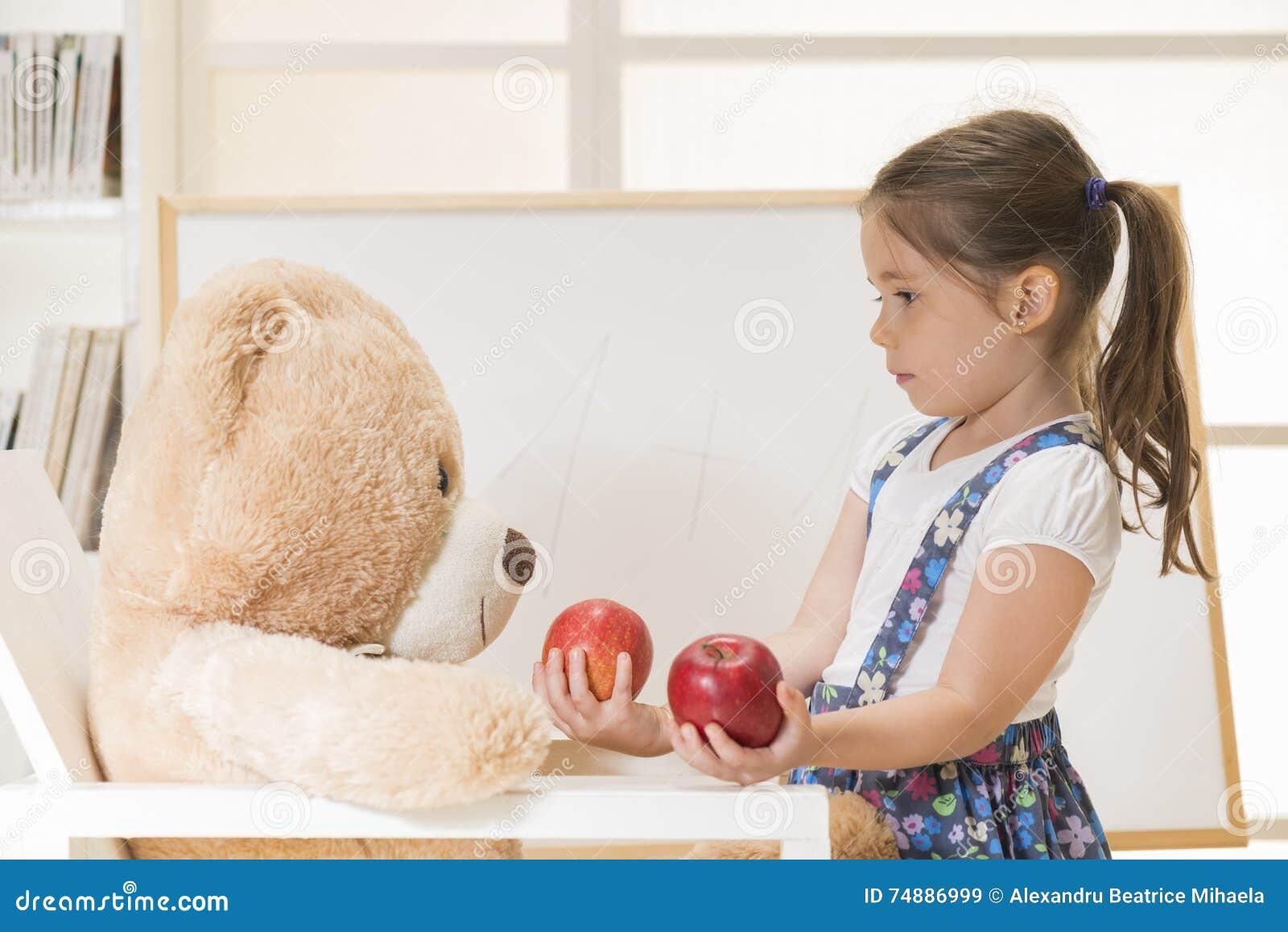 Menina que ensina seu amigo do urso do brinquedo contar com maçãs, tiro interno