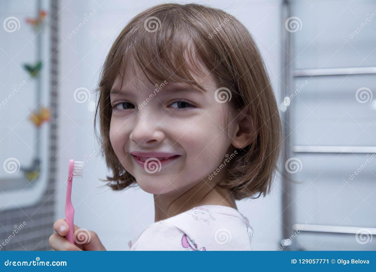 Menina que escova seus dentes no banheiro