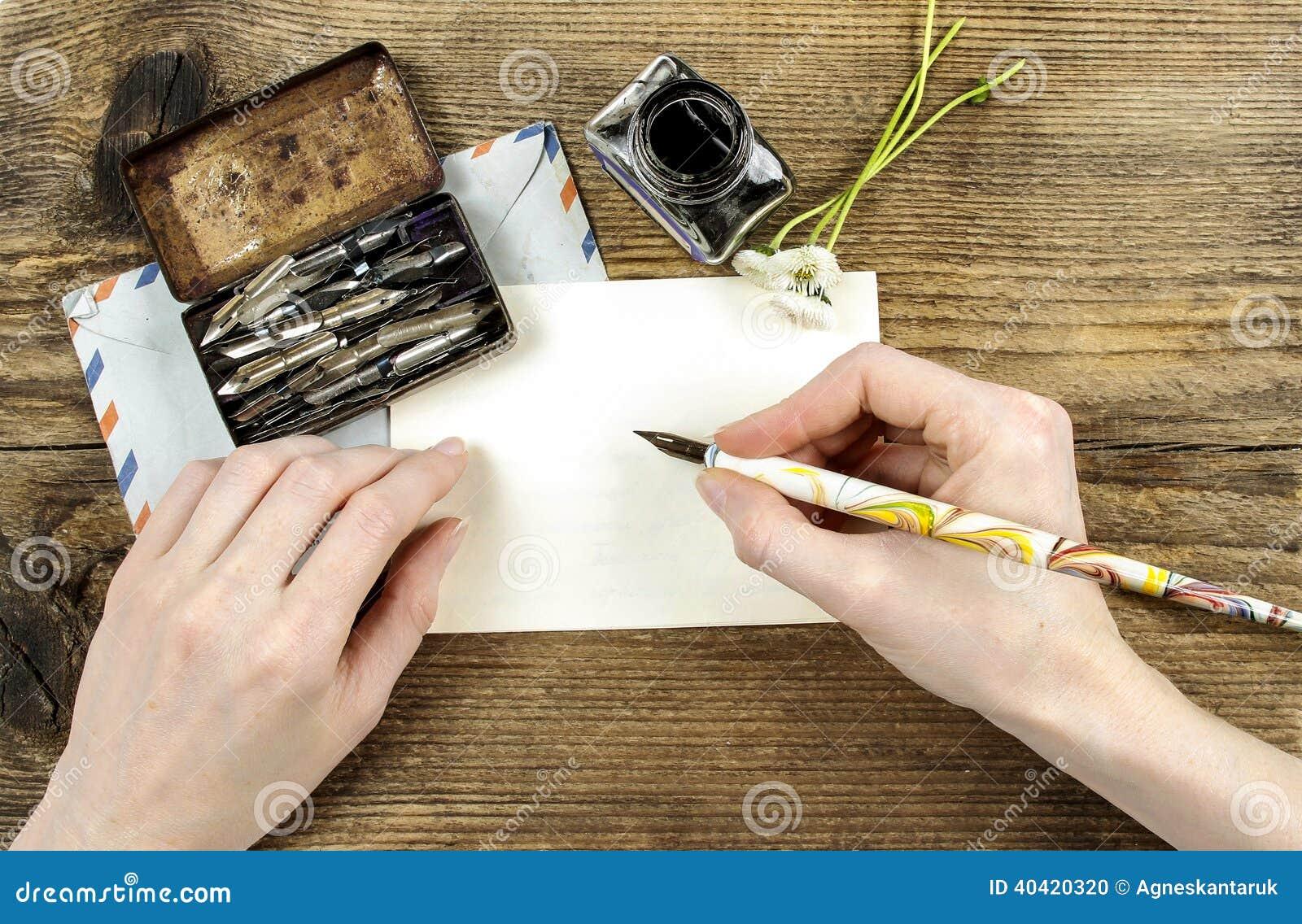 Menina que escreve uma letra com pena da tinta
