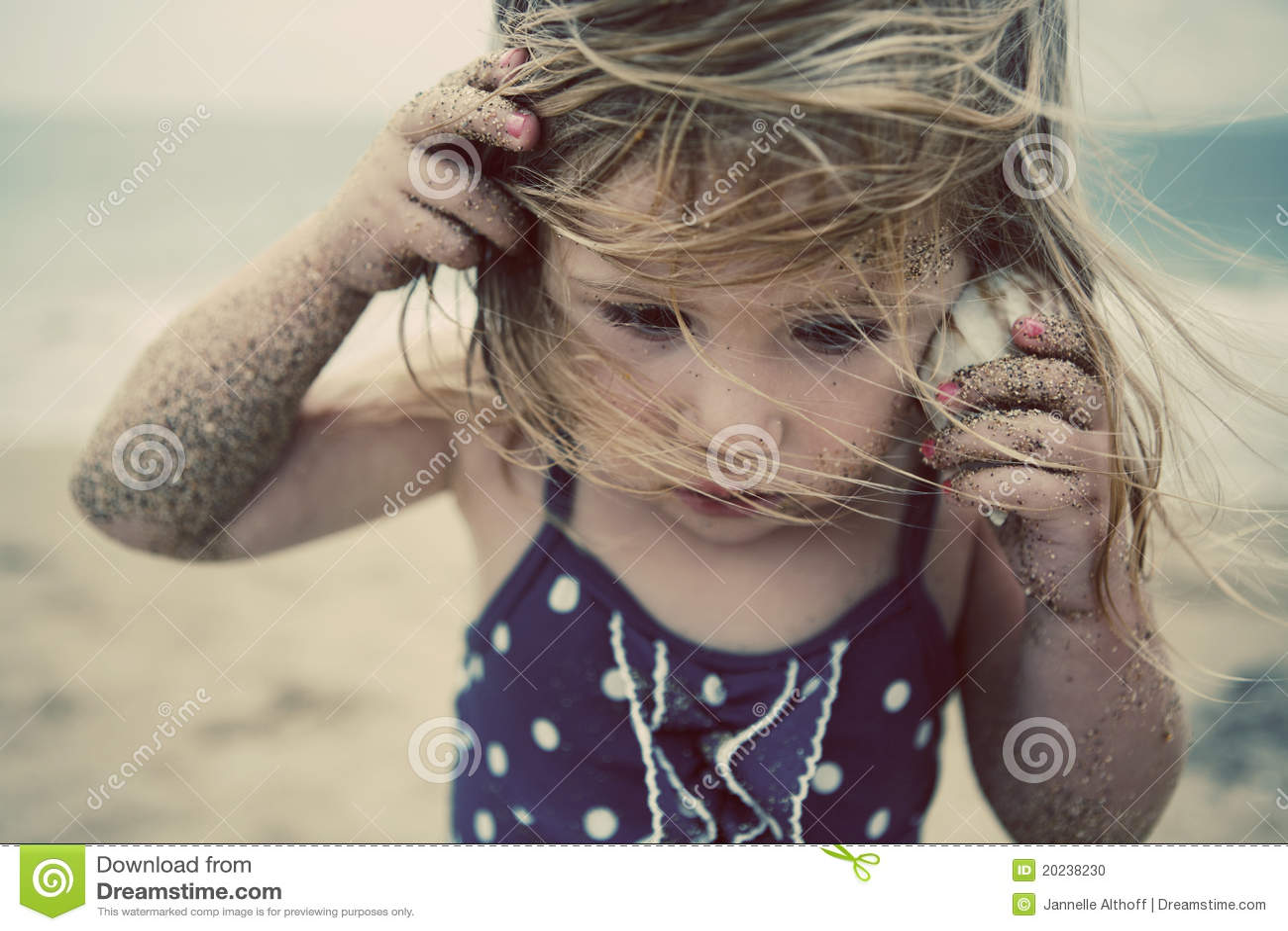 Menina que escuta o escudo do mar