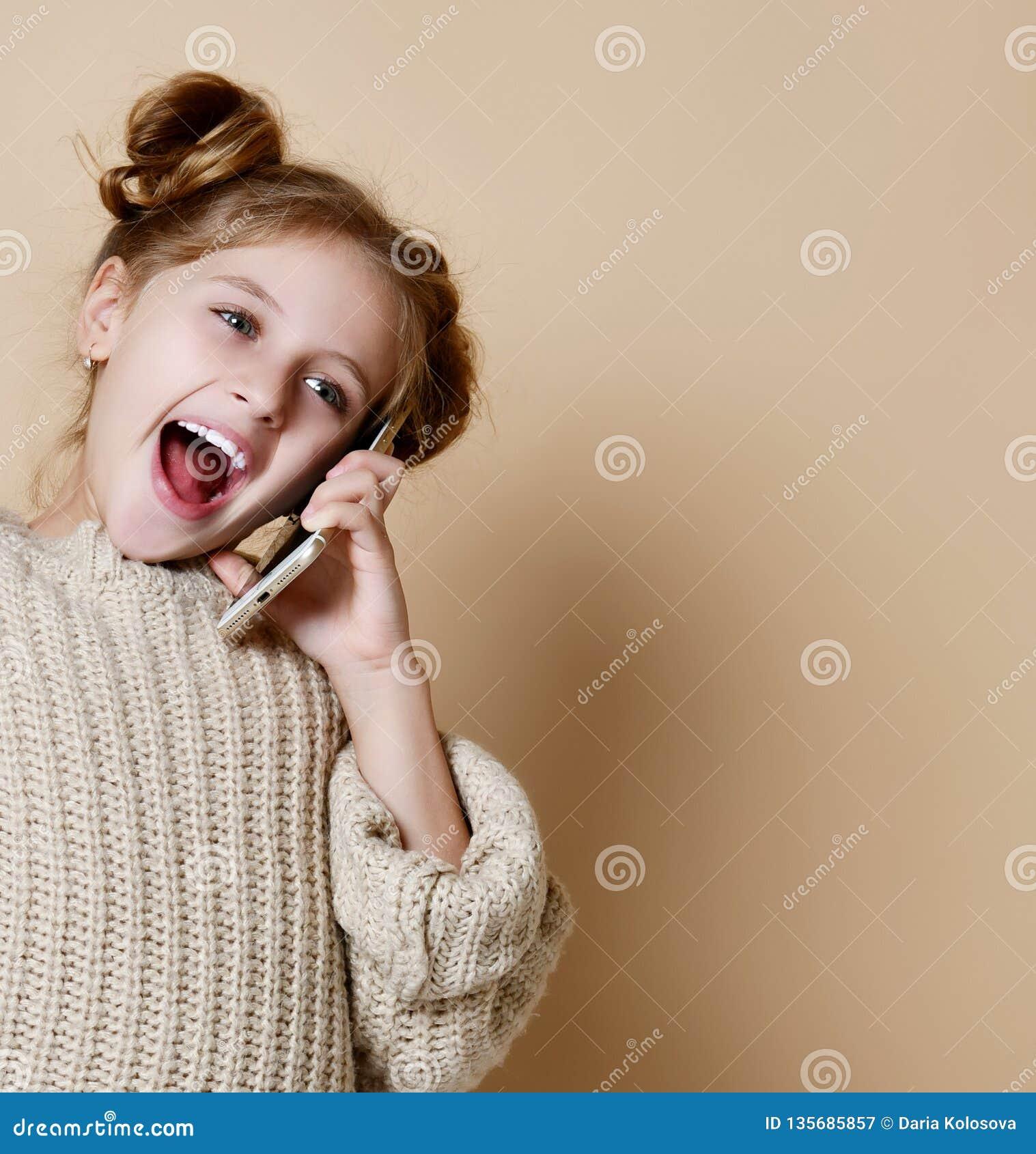 Menina que fala pelo telefone celular, fundo nude