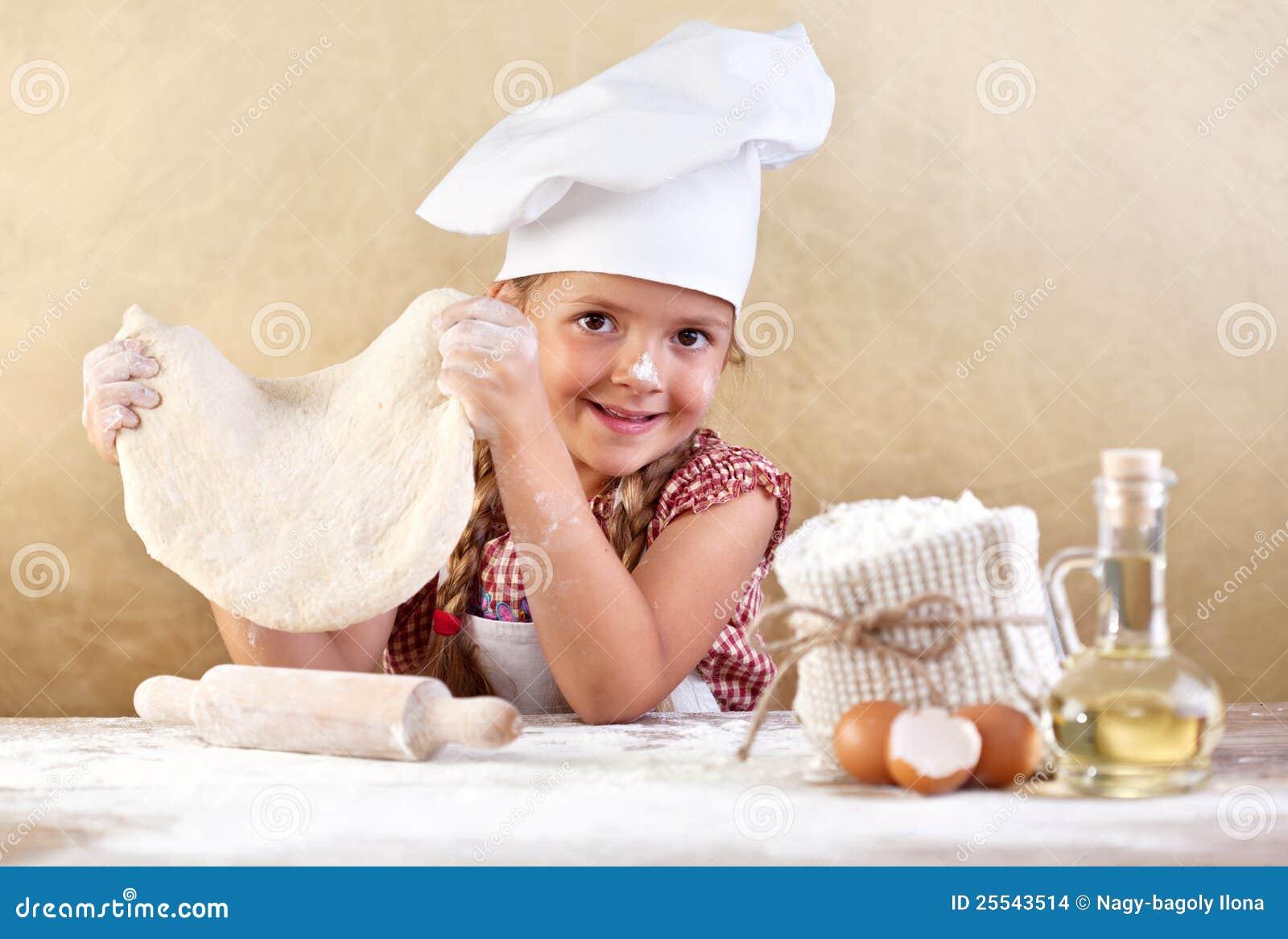 Menina que faz a massa de pão da pizza ou da massa