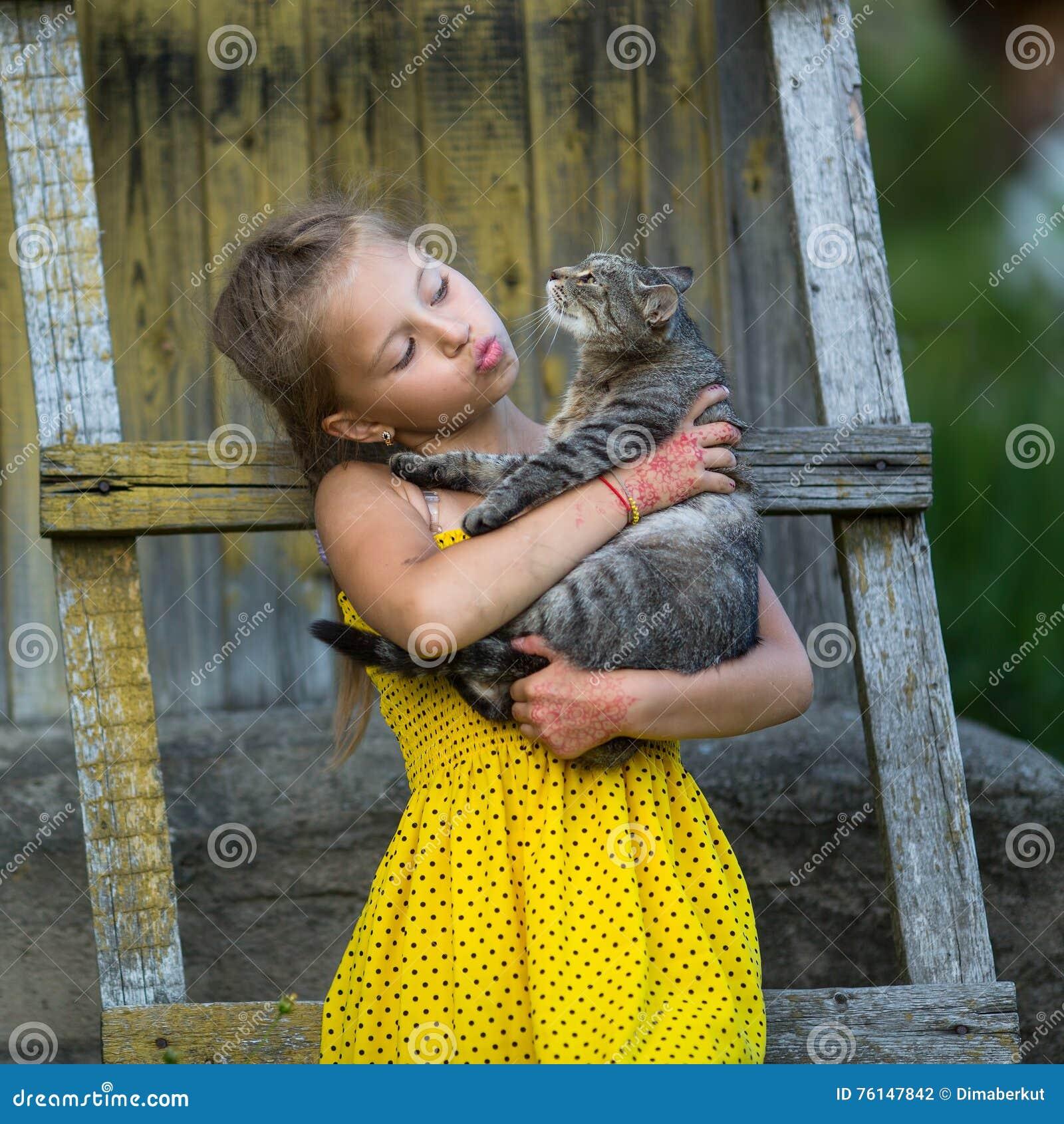 Menina que guarda um gato em seus braços