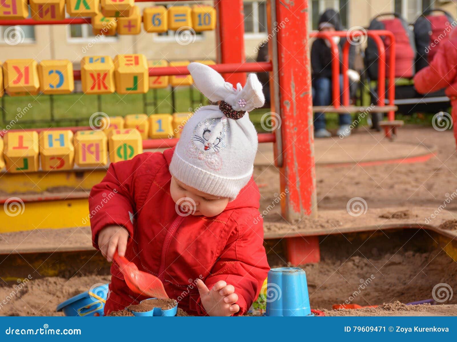 Menina que joga com areia