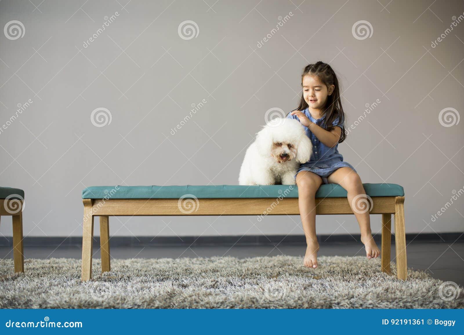 Menina que joga com caniche branca