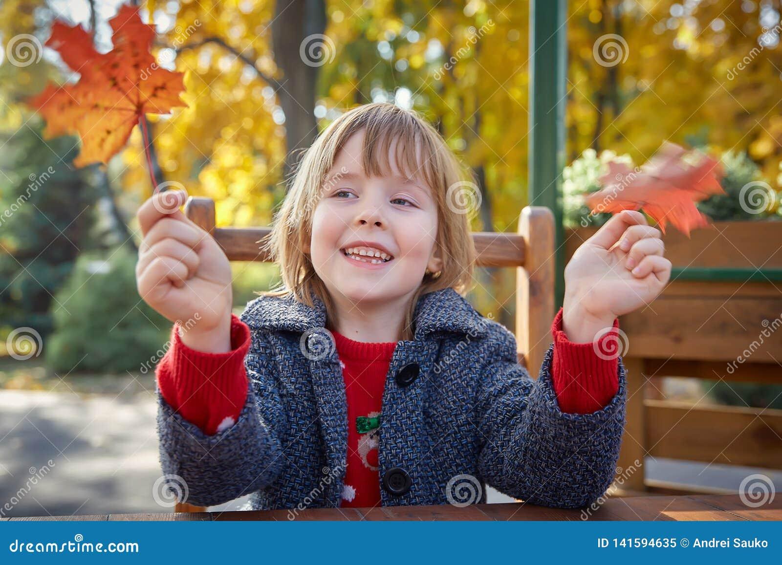 Menina que joga com folhas de outono