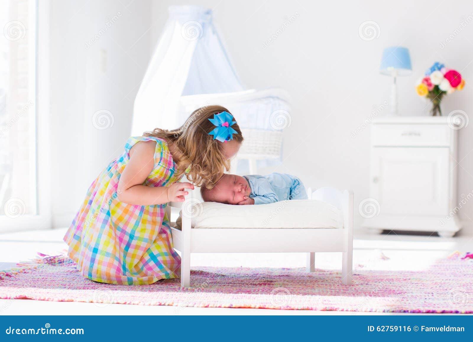 Menina que joga com o irmão recém-nascido do bebê