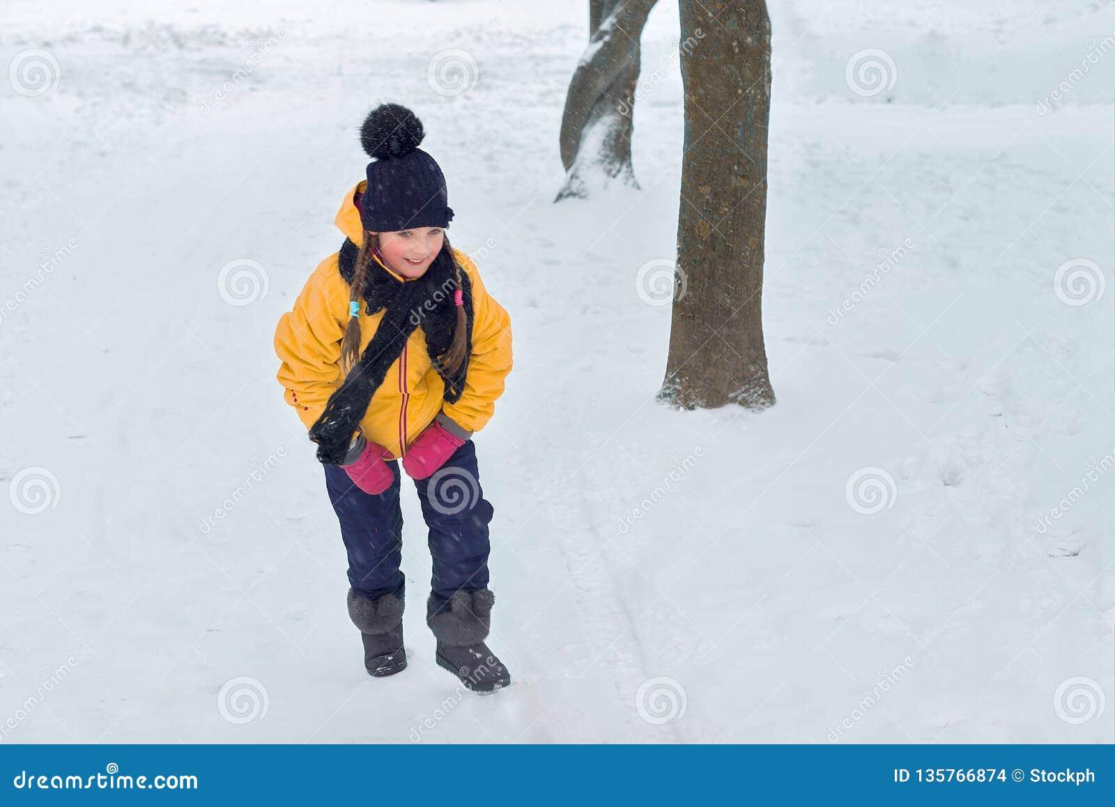 Menina que joga em um monte do inverno