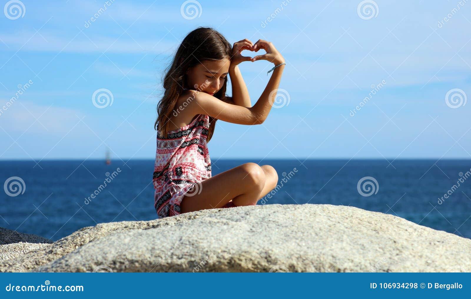 Menina que joga na parte dianteira de oceano no mar do penhasco do recurso de Los Cabos México
