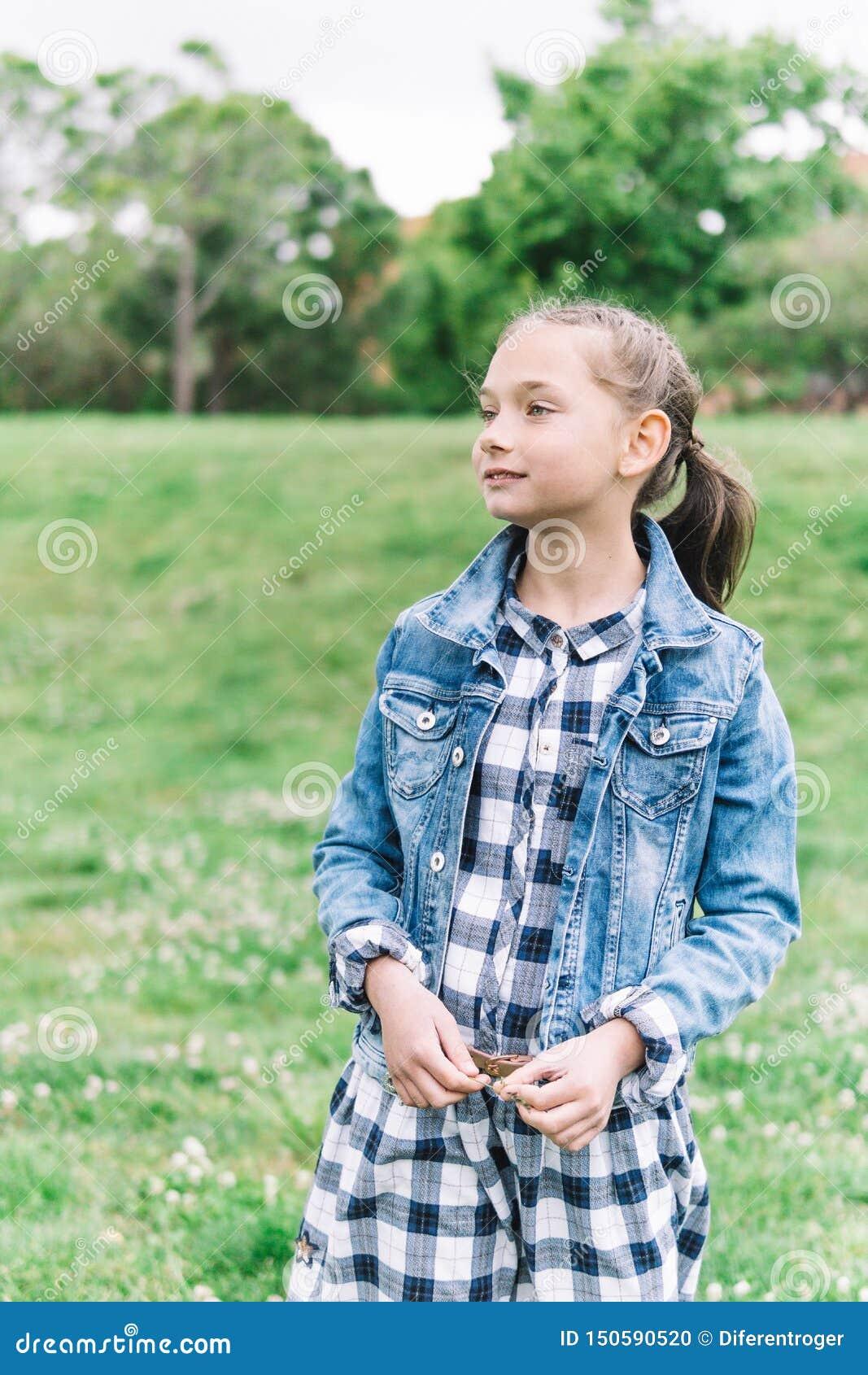Menina que joga no parque no fundo verde