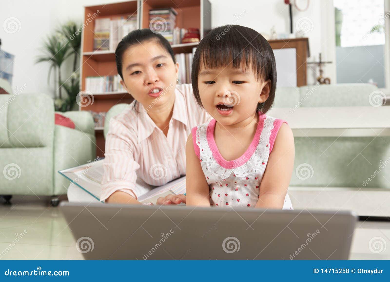 Menina que joga o portátil