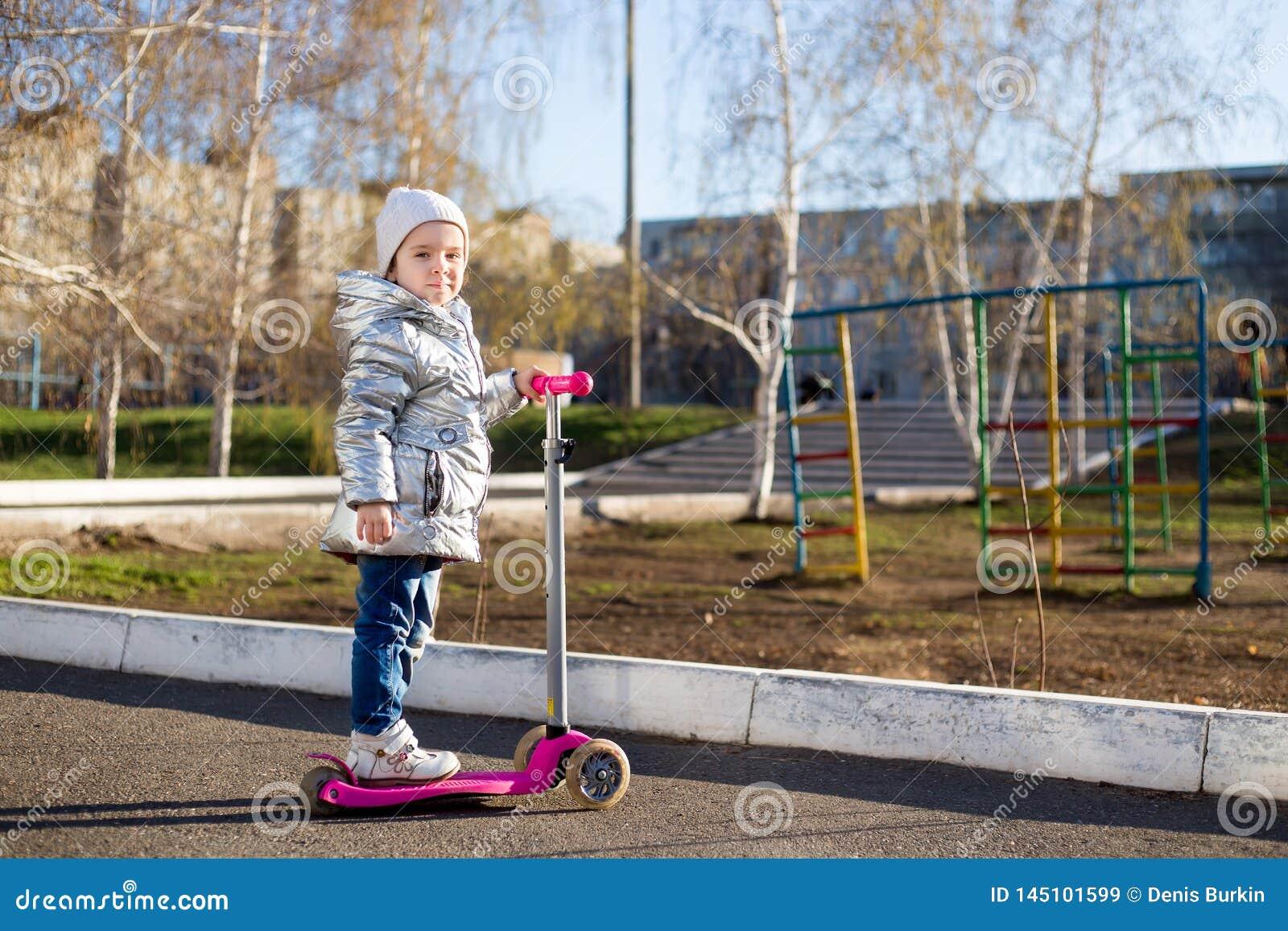 Menina que monta um  trotinette  no parque em um dia de mola ensolarado Lazer ativo e esporte exterior para crian?as