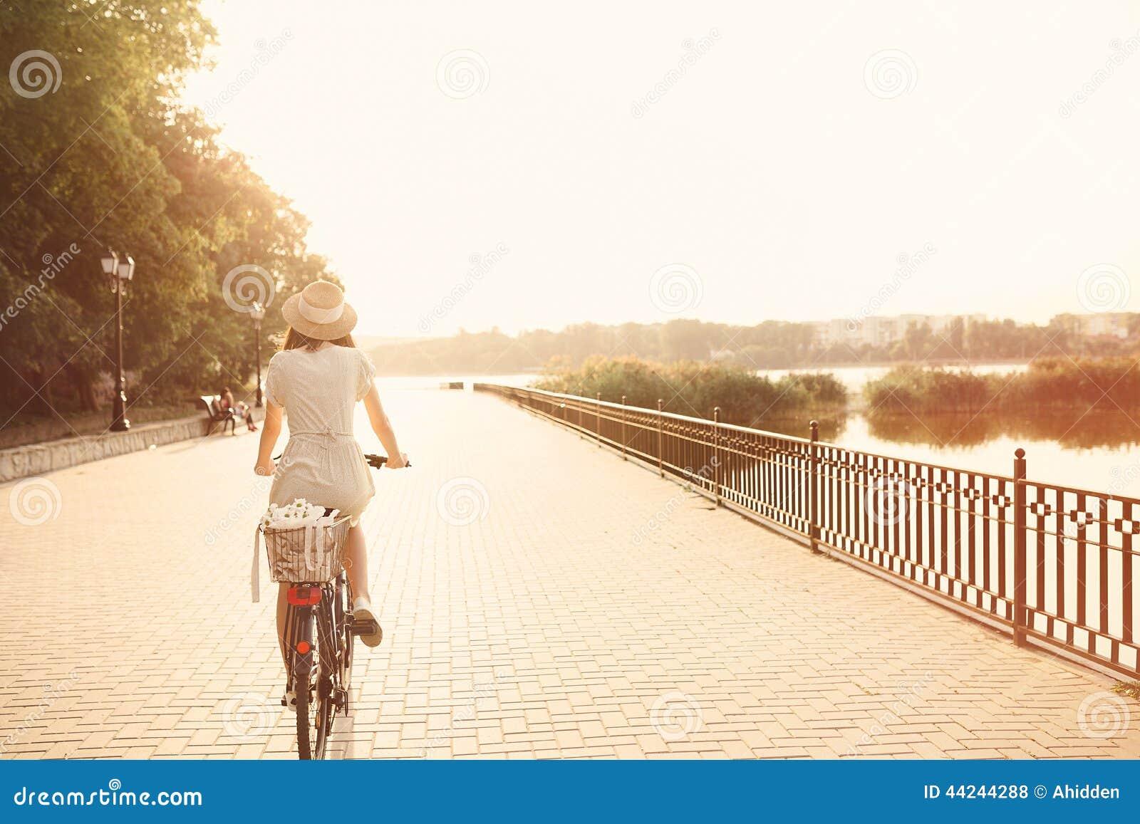 Menina que monta uma bicicleta no parque perto do lago