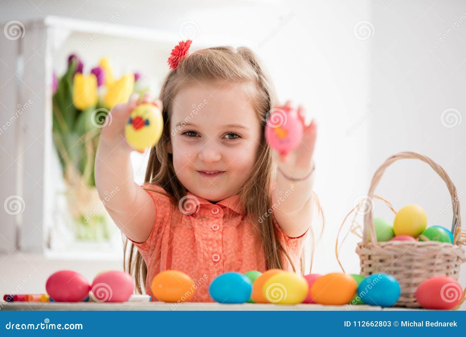 Menina que mostra lhe ovos coloridos pintados à mão