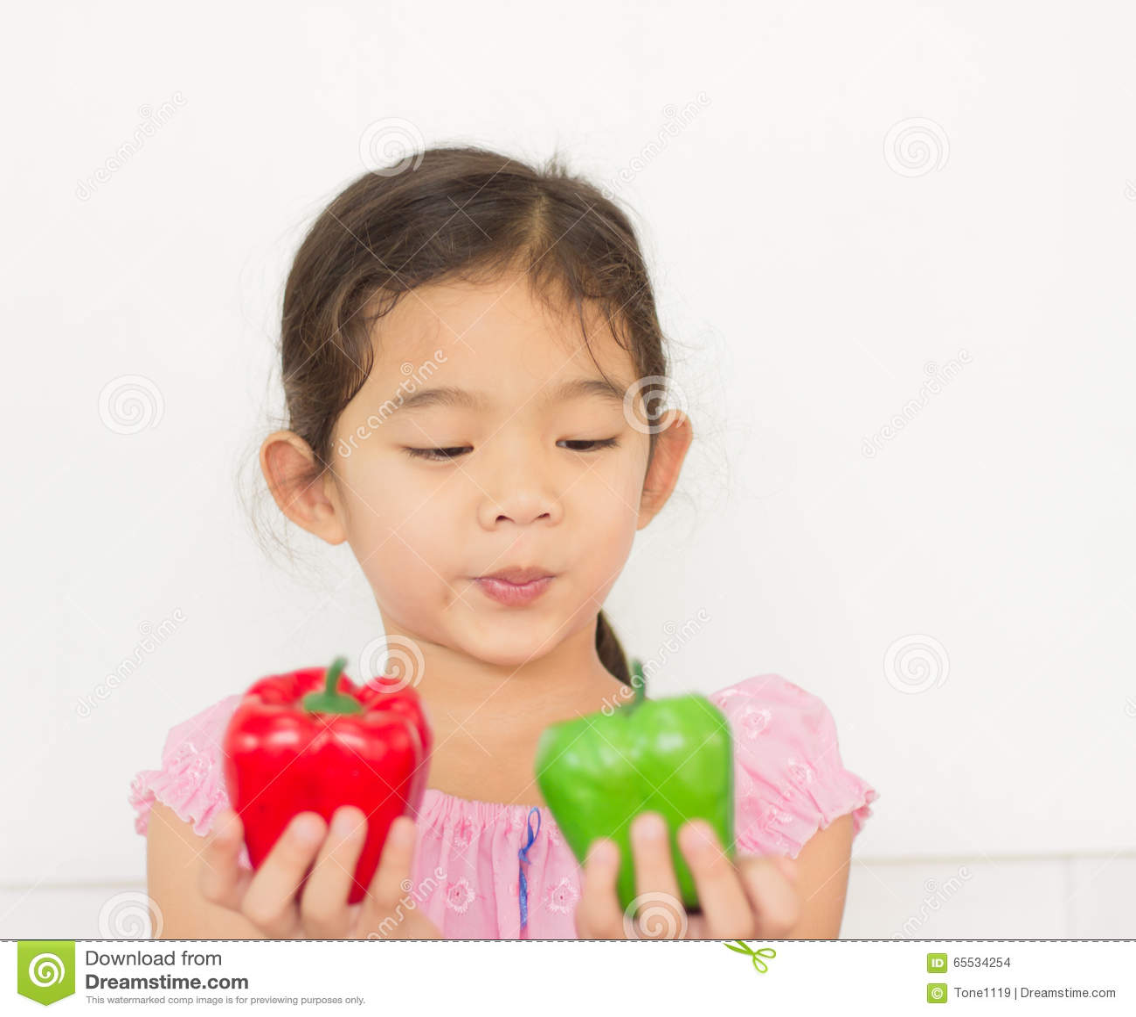 Menina que olha o fruto da pimenta de sino em sua mão
