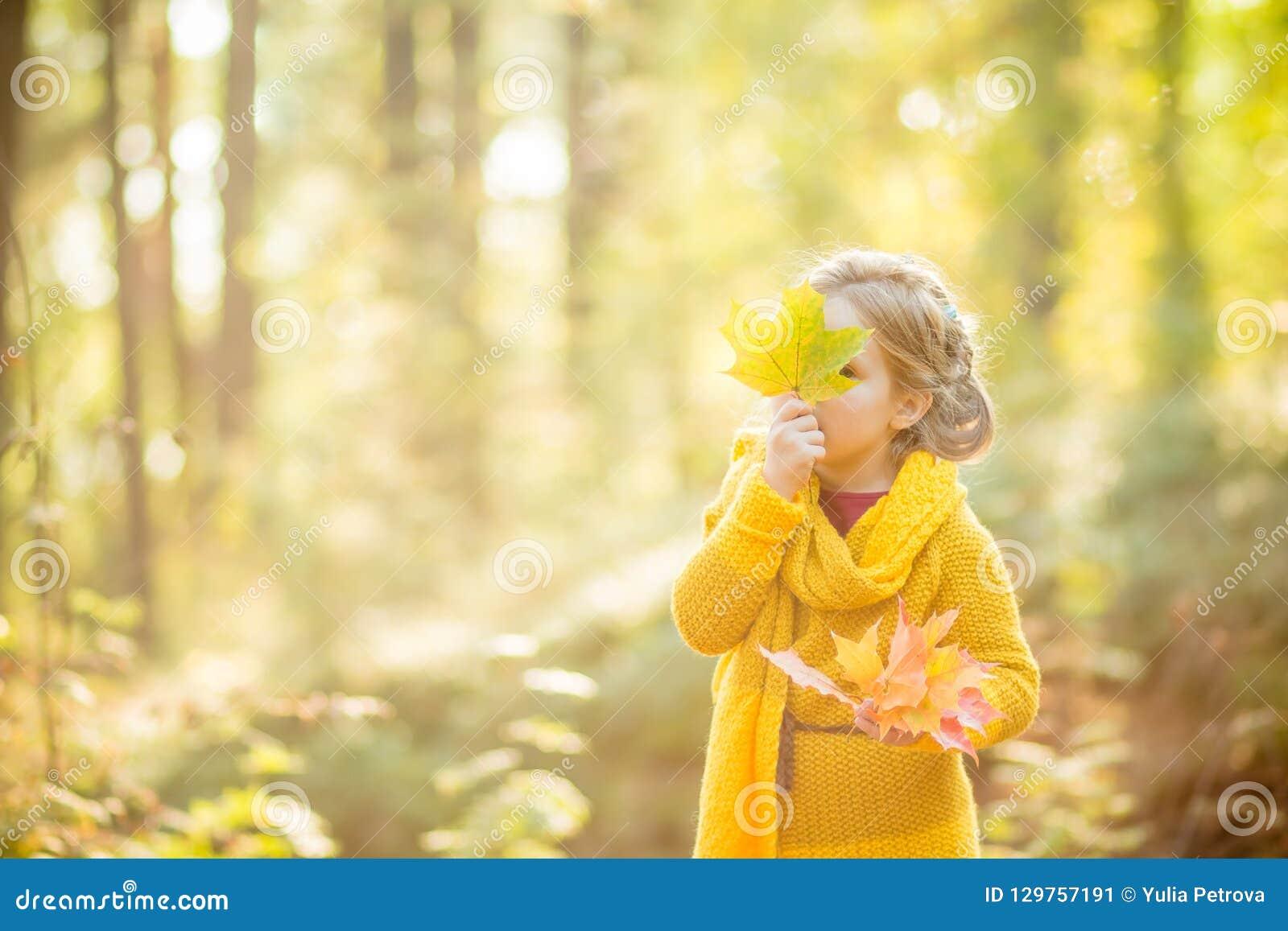 Menina que olha para fora atrás de um ramalhete das folhas de outono Autumn Portrait Conceito do outono Tempo da infância cute